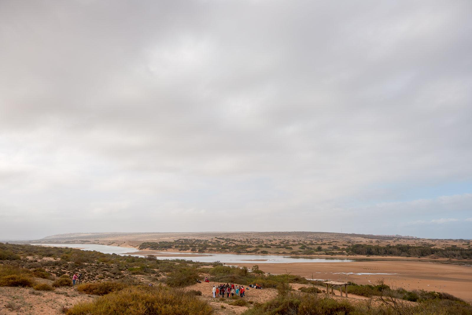 Bild einer nahezu ausgetrockneten Flusslandschaft mit einer kleinen Menschgruppe im Vordergrund