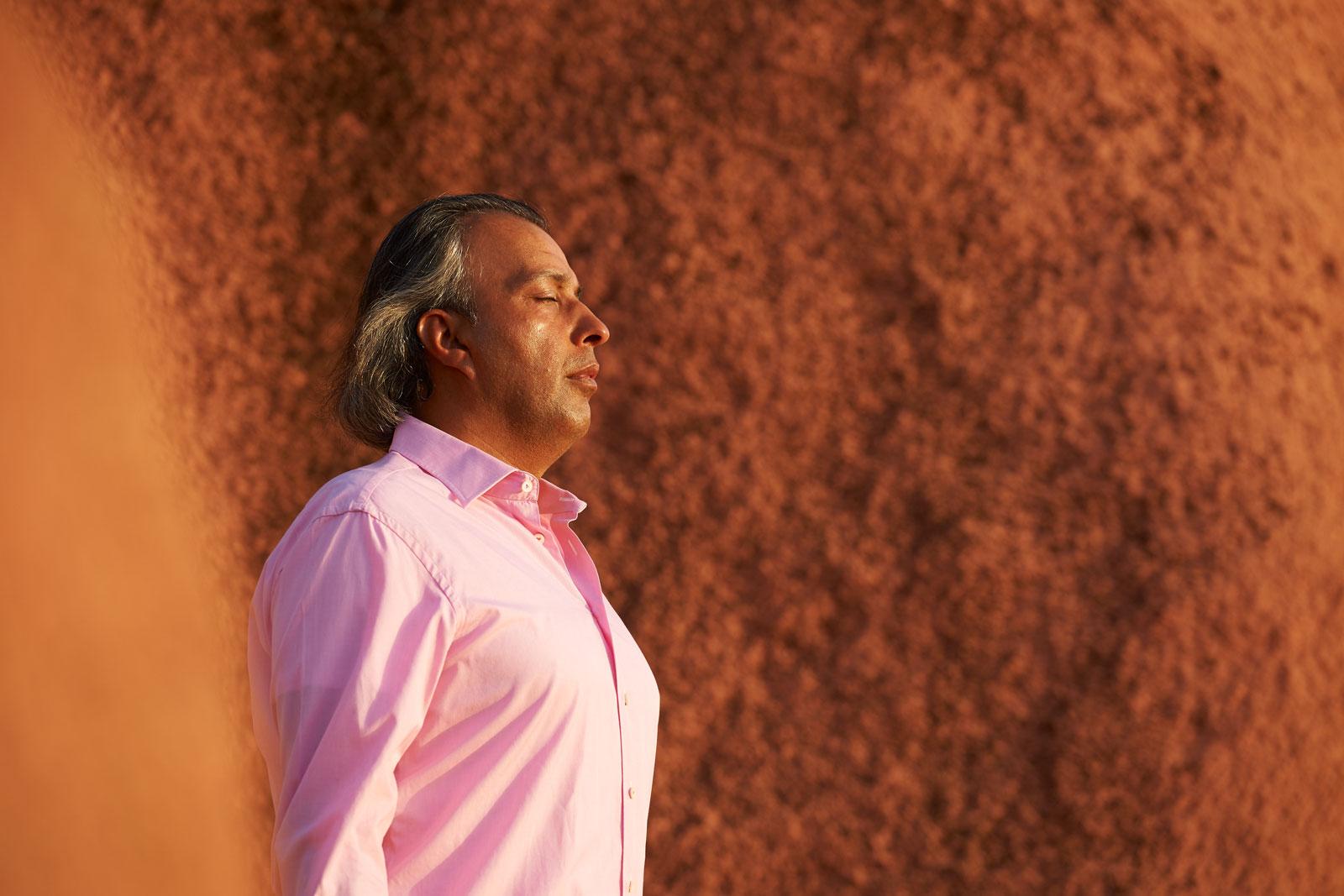 Bild eines meditierenden Mannes zwischen riesigen roten Felsen in Marokko