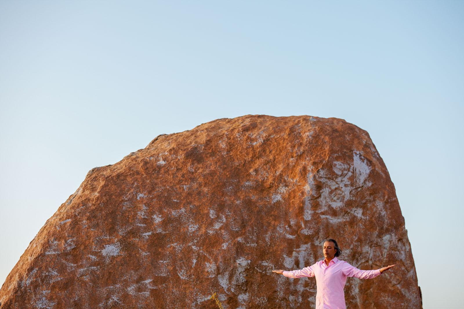 Bild eines segnenden Mannes vor eine roten Felskuppe