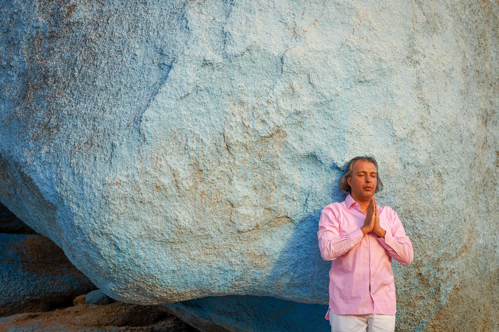 Portrait eines segnenden Mannes vor einem blauen Felsen in Tafraoute, in den Bergen des Antiatlas Gebirges in Marokko