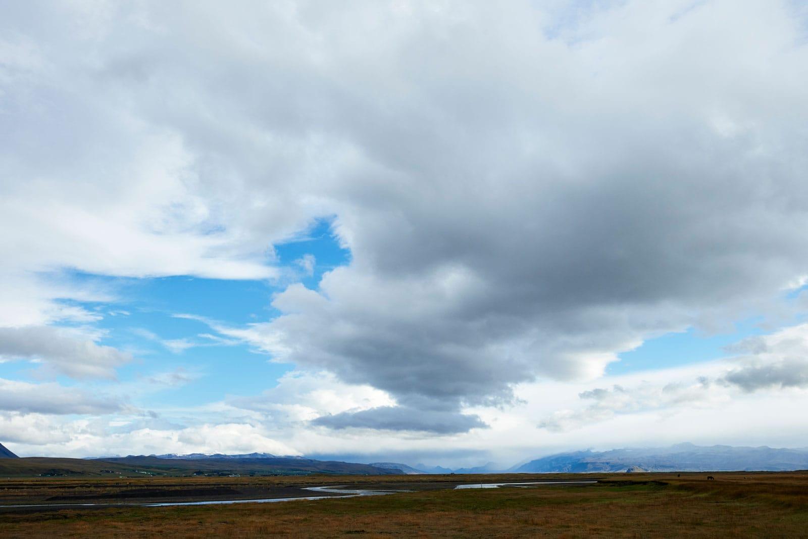 Wolkenhimmel über mäanderndem Fluss