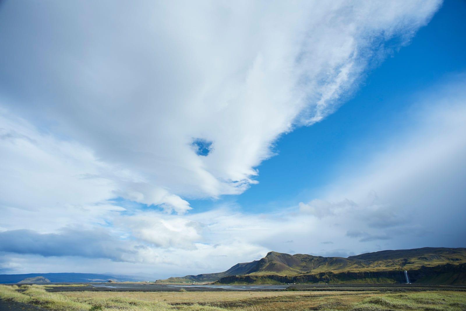 Wolkenhimmel über Berglandschaft mit Wasserfall