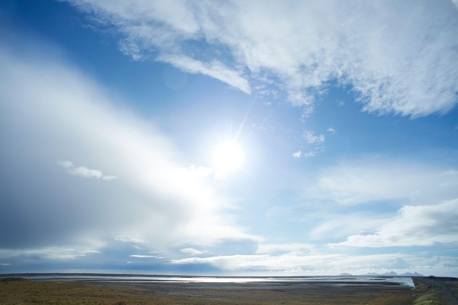 wolkiger Sonnenhimmel über Seenlandschaft