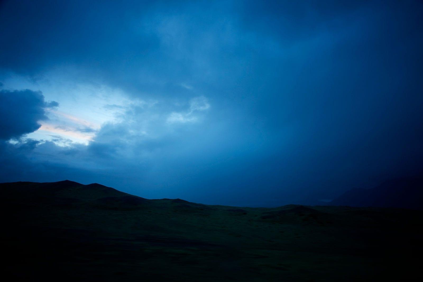 dunkelblauer Wolkenhimmel über dunkler Landschaft