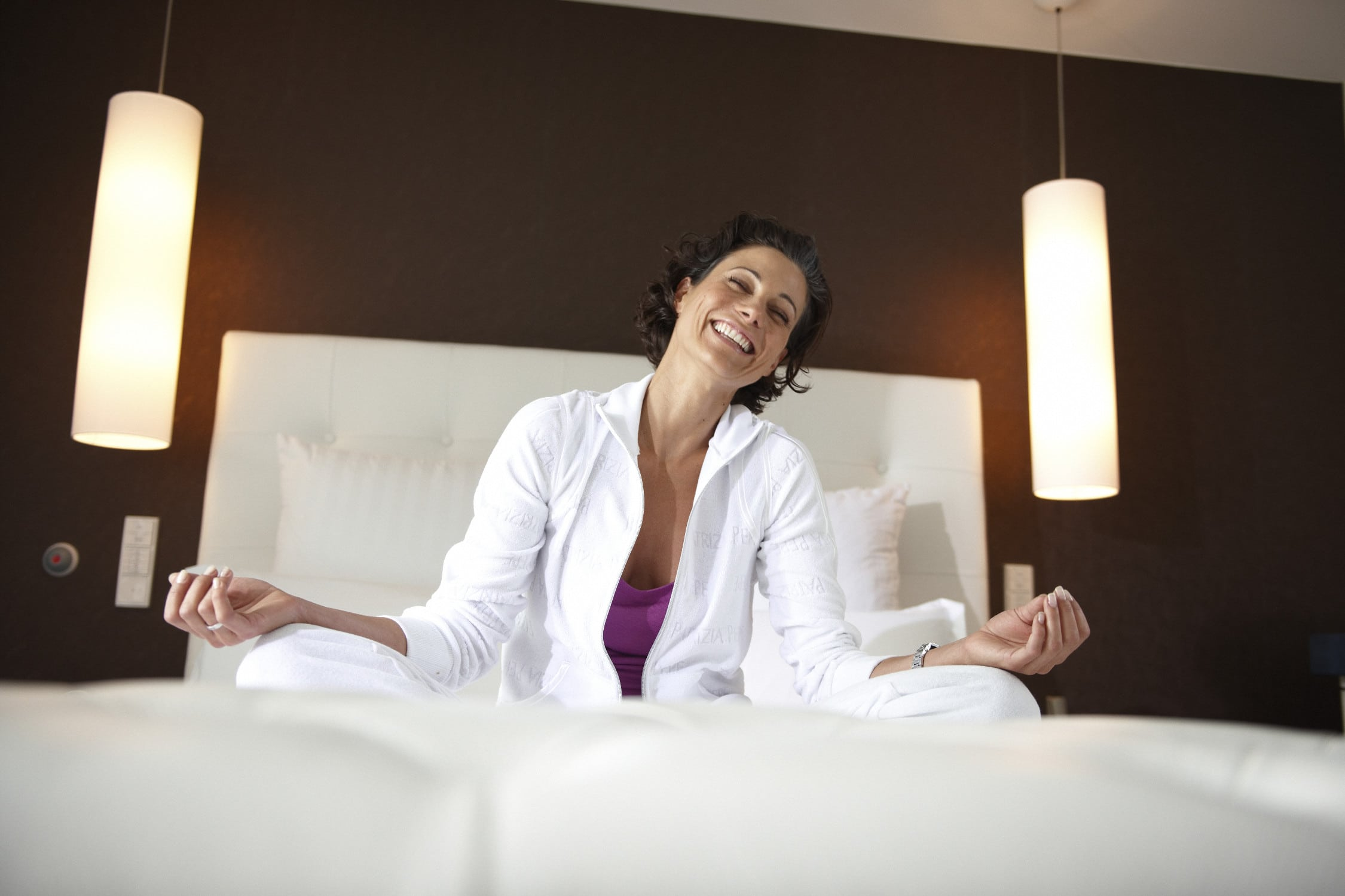 lachende sportliche Frau sitzt auf dem Bett in ihrem Schlafzimmer