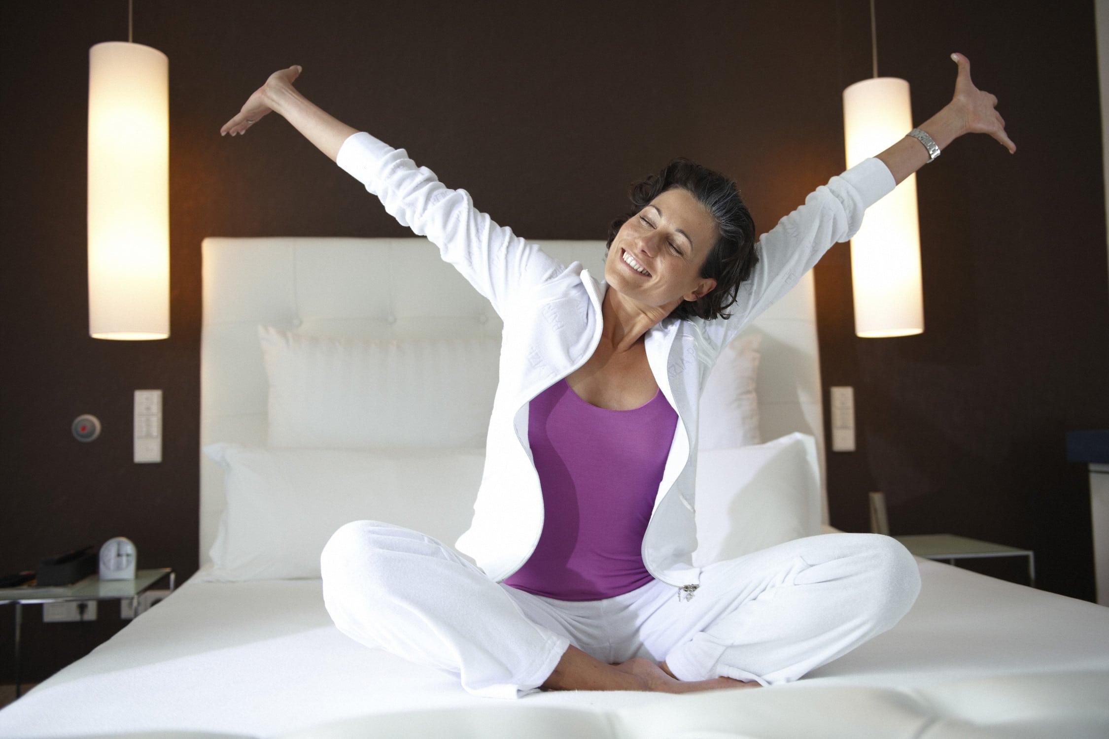 Schöne Frau steckt sich in ihrem eleganten Schlafzimmer