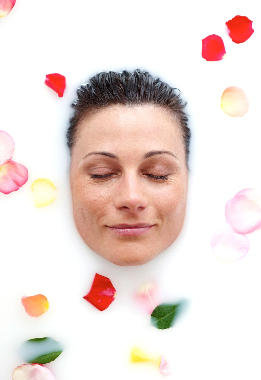 Das relaxte Gesicht einer Schönen umringt von Rosenblättern geniesst das Milchbad