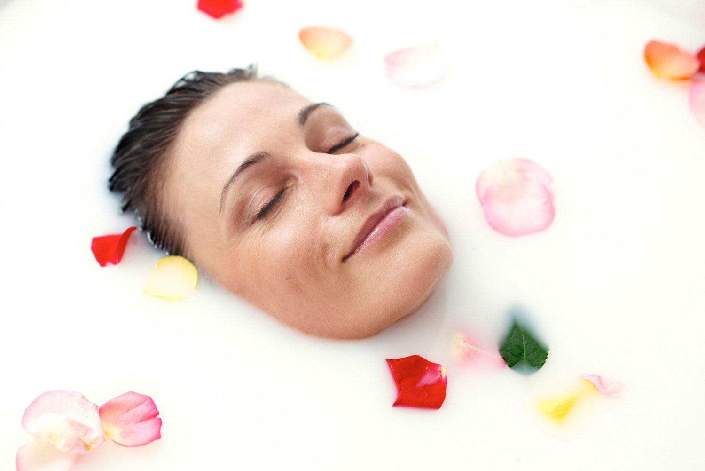 Das schöne Gesicht einer Frau lugt aus einem mit Rosenblätter umgebenen Milchbad