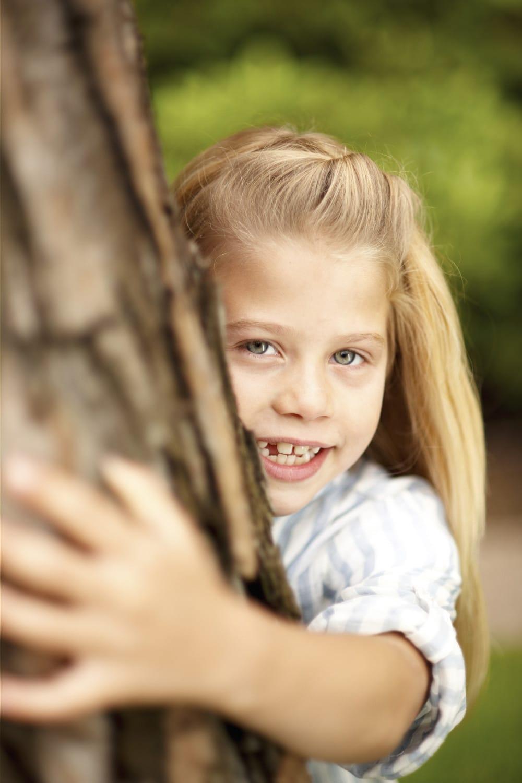 Junges Mädchen umarmt liebevoll einen Baum in die Kamera blickend