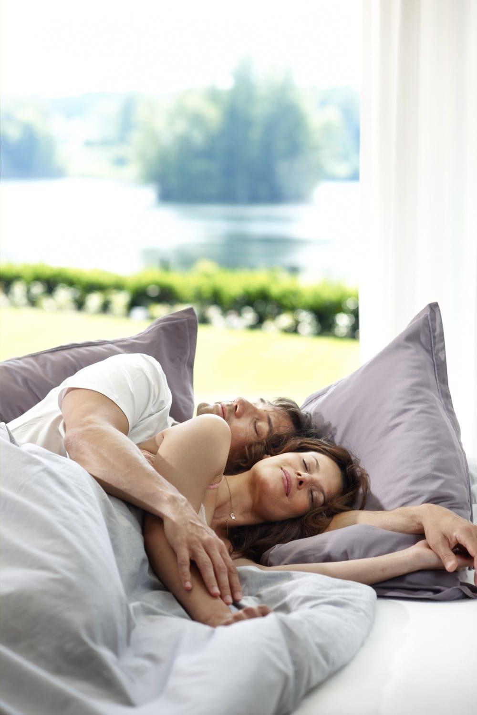Eigentümerehepaar räckelt sich Bett mit Blick auf den See
