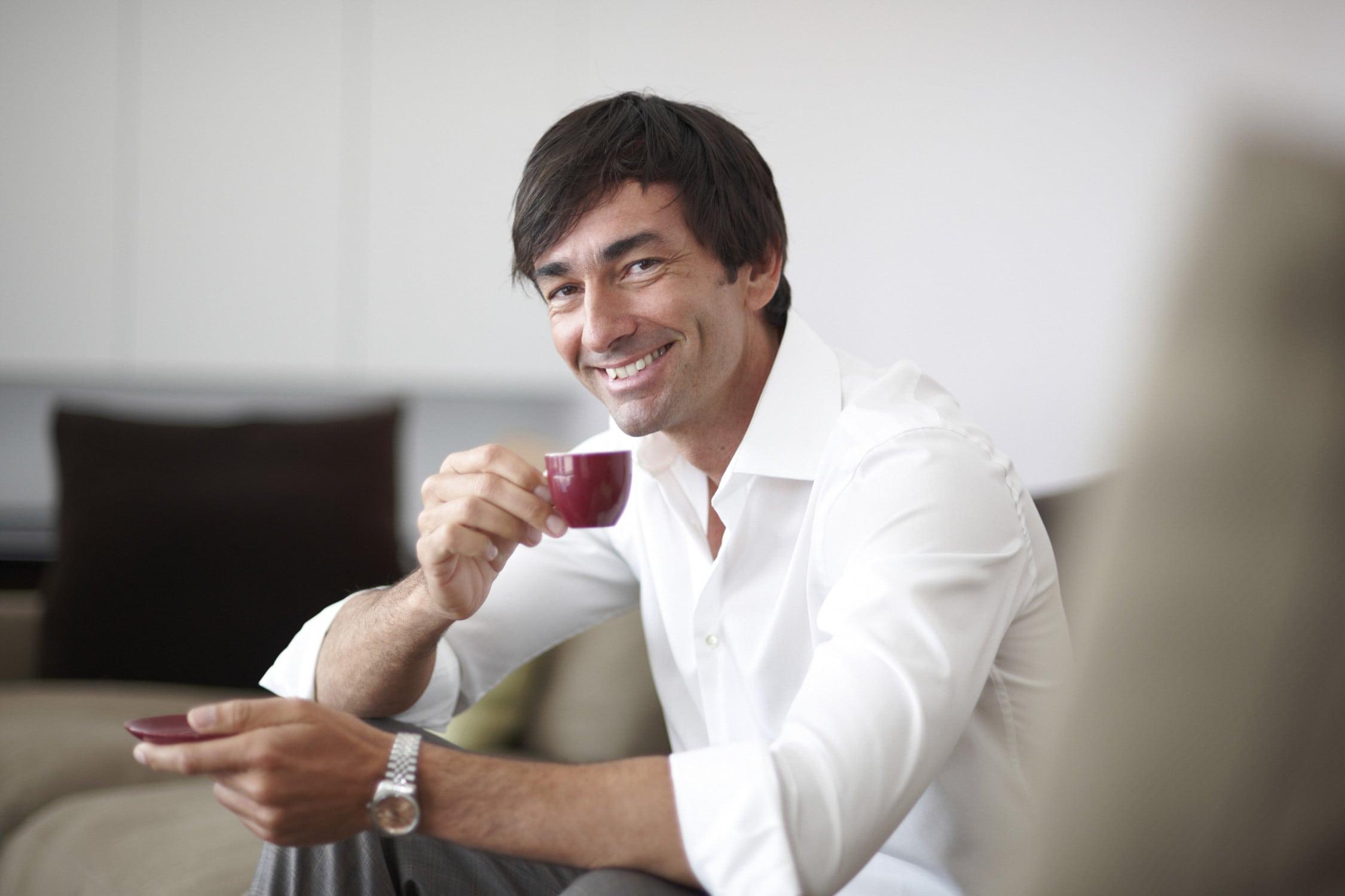 Entspannter Mann genießt seinen Kaffe auf seiner Couch