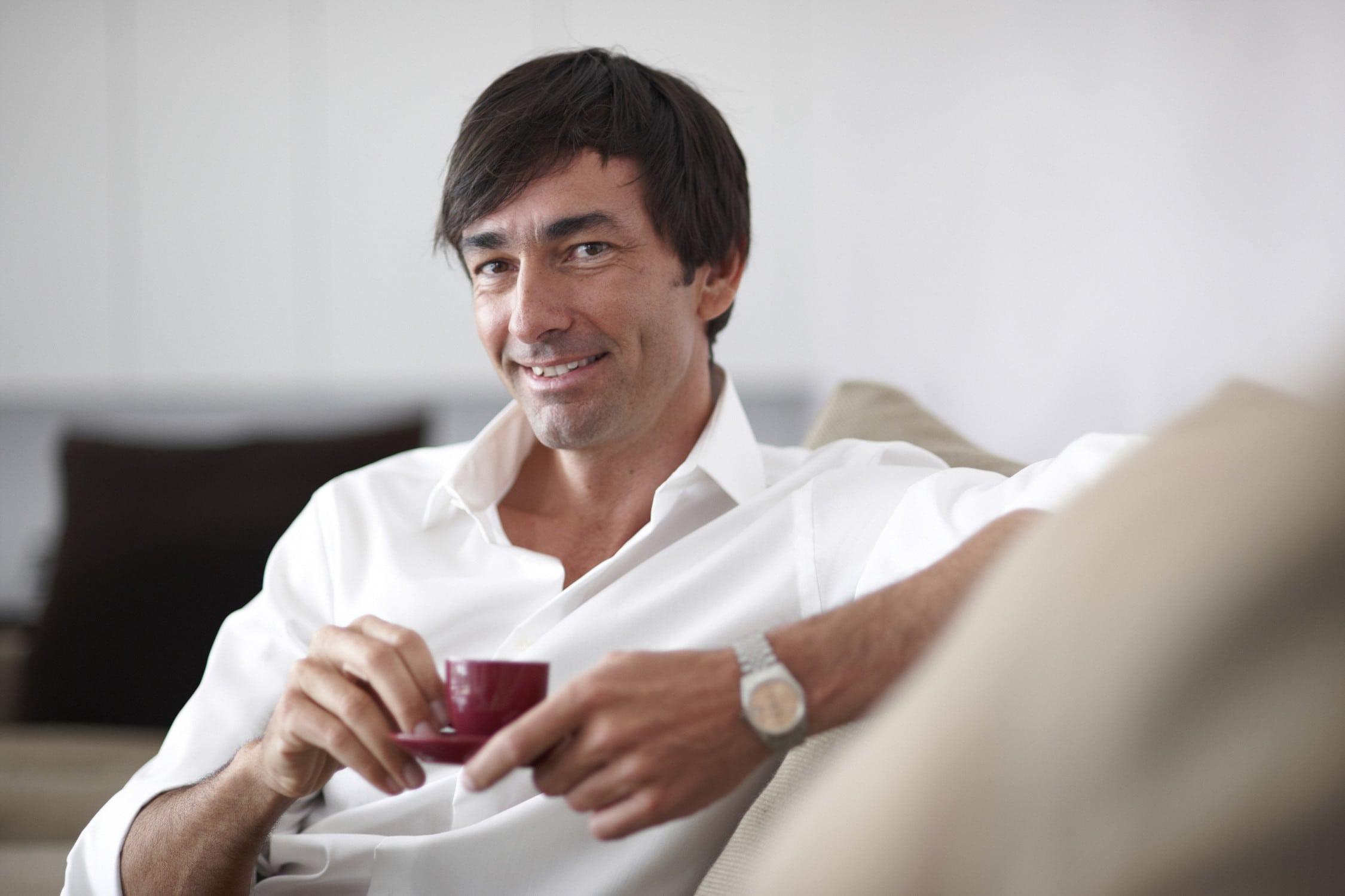 Relaxtet Typ genießt eine Tasse Kaffee auf dem Sofa sitzend