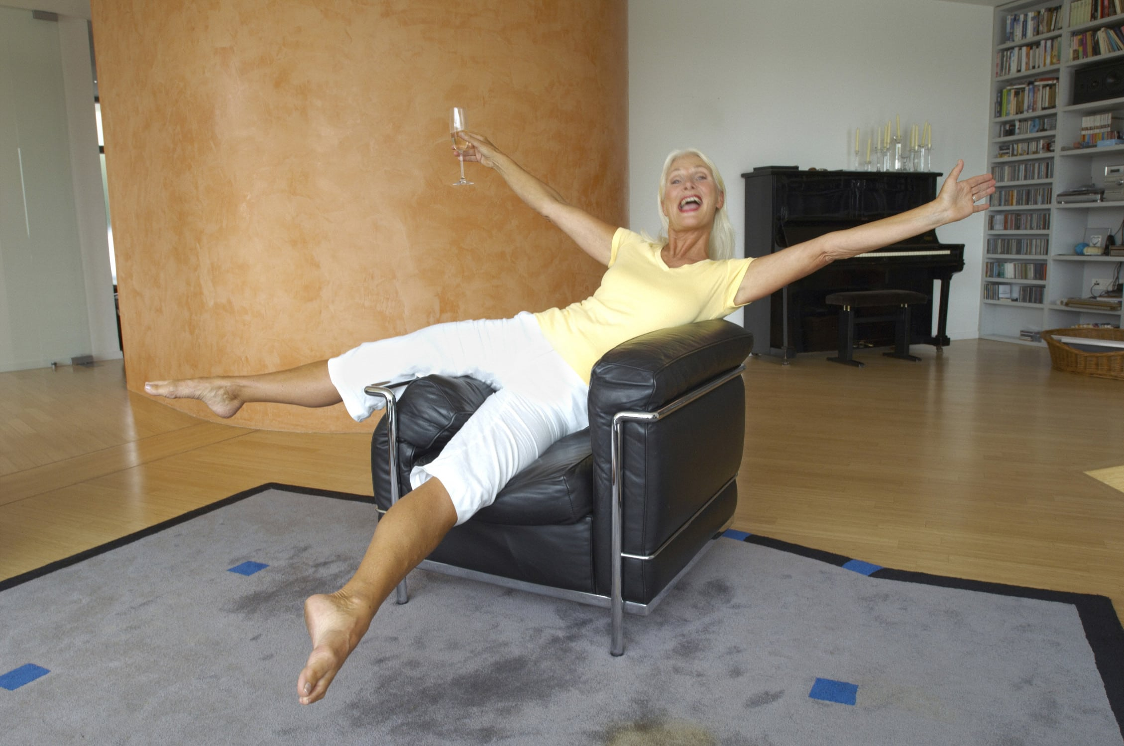 Sehr agile Seniorin reckt und steckt sich auf einem Sessel im Wohnzimmer
