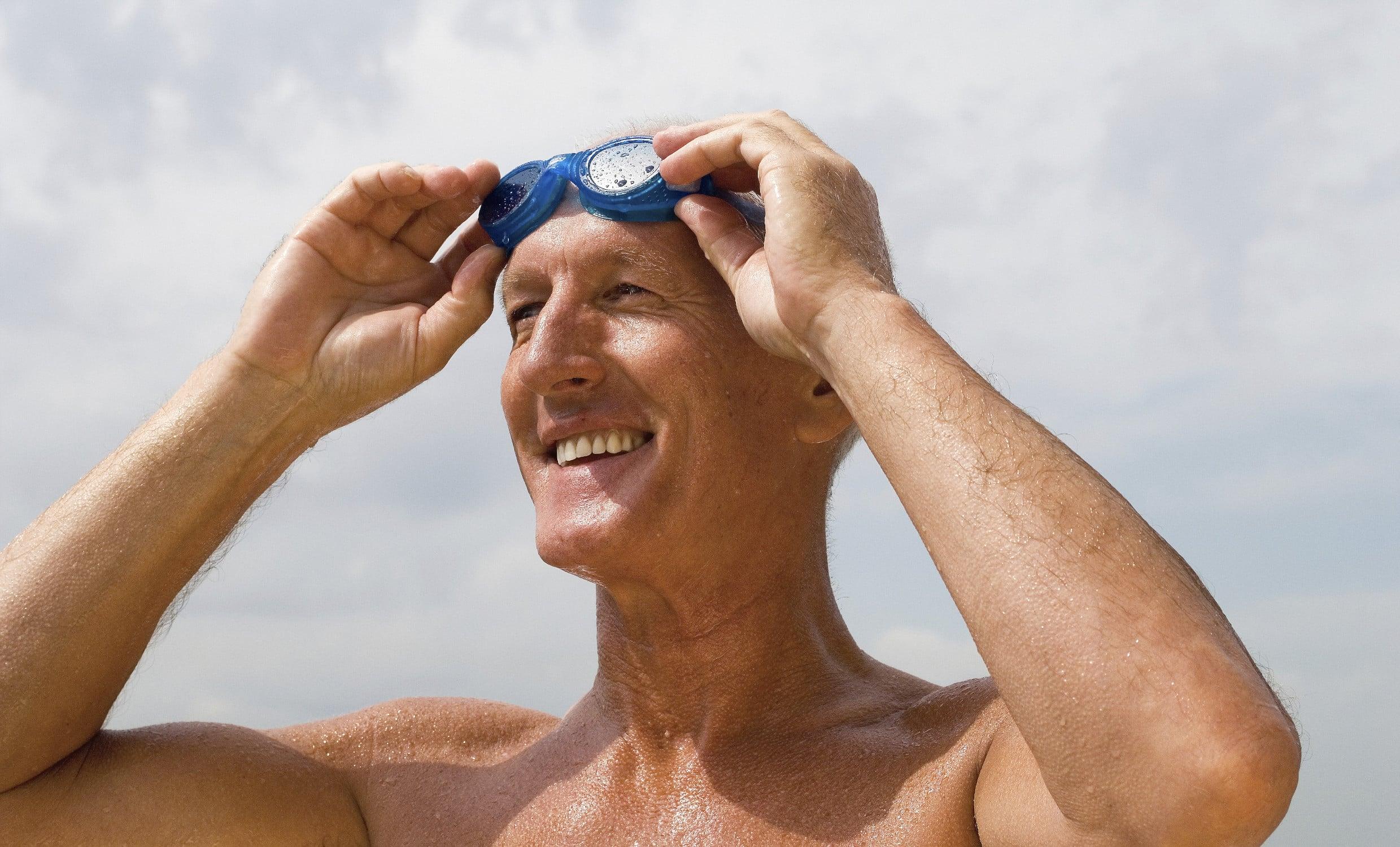 Gutgelaunter, sportlicher Senior rückt seine Schwimmbrille zurecht