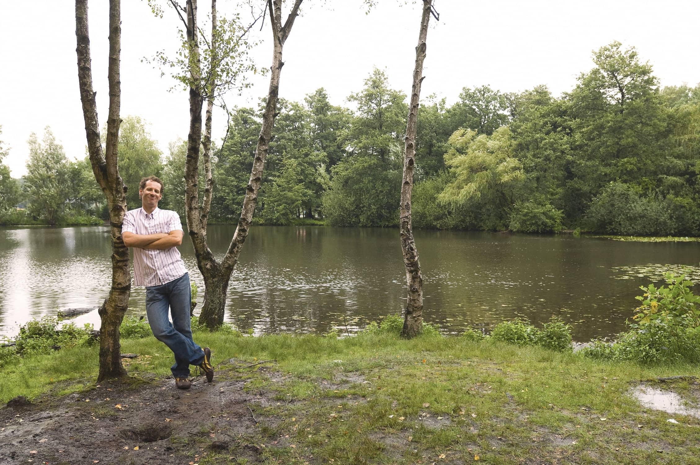 Empathischer cooler Typ lehnt an einem Baum auf seinem Grundstück am See
