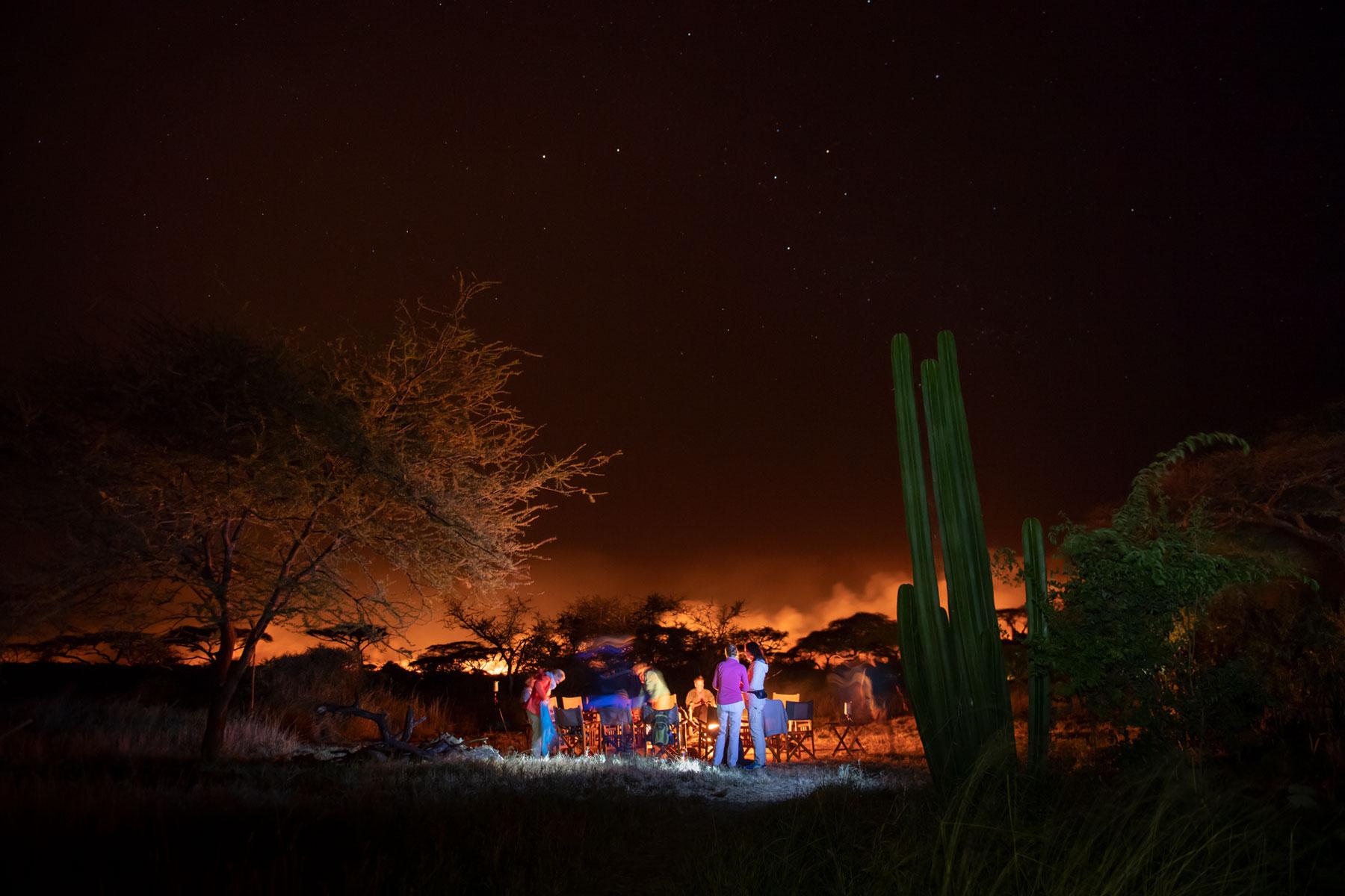 Bild einer sternenklaren Nachtaufnahme mit Menschen in der Bildmitte und brennender Serengeti im Hintergrund