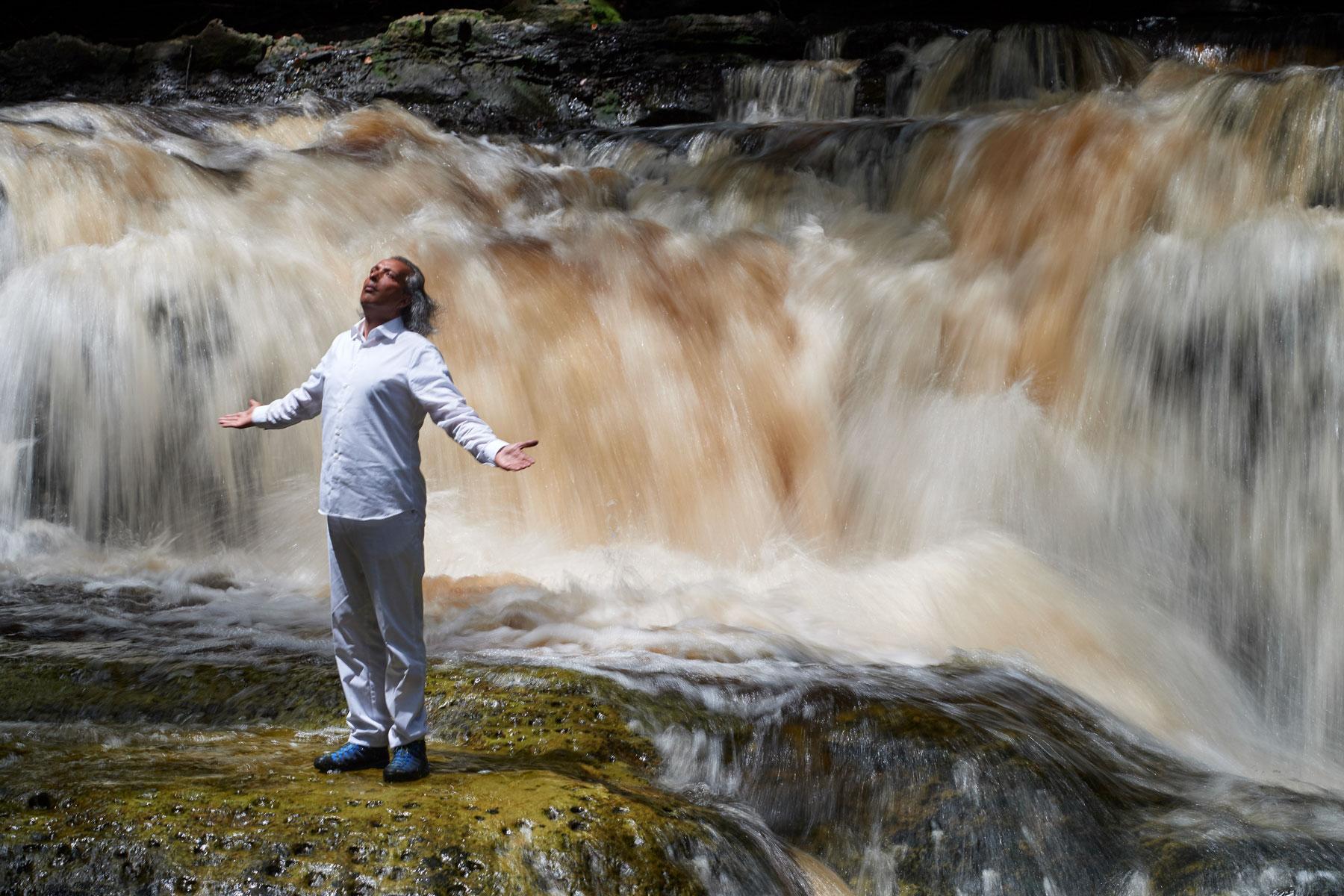 Heiliger Mann in Weiß segnet mit ausgebreiteten Armen das Wasser vor einem Wasserfall stehend