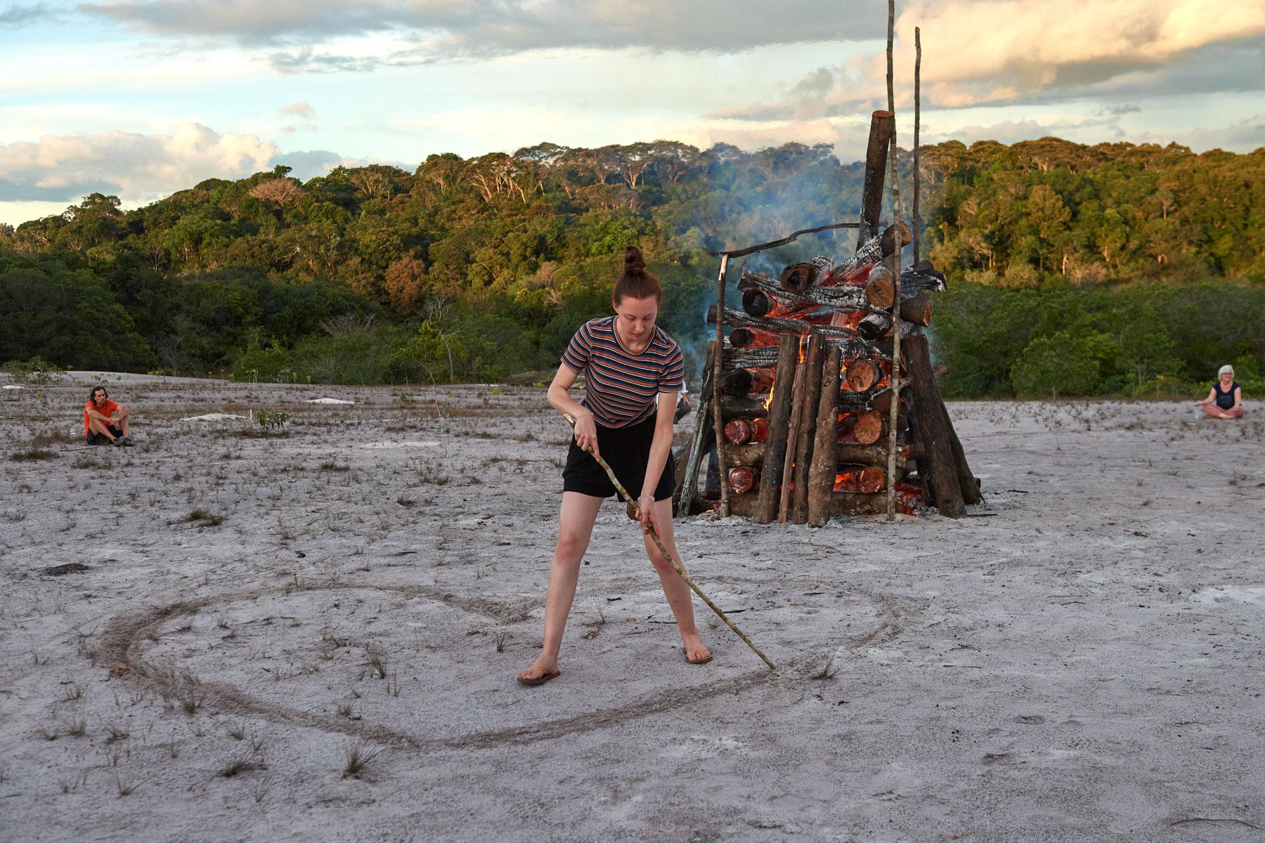 Foto einer jungen Frau, die vor einem brennenden Holzstapel mit einem Stock ein Herz in den Sand malt