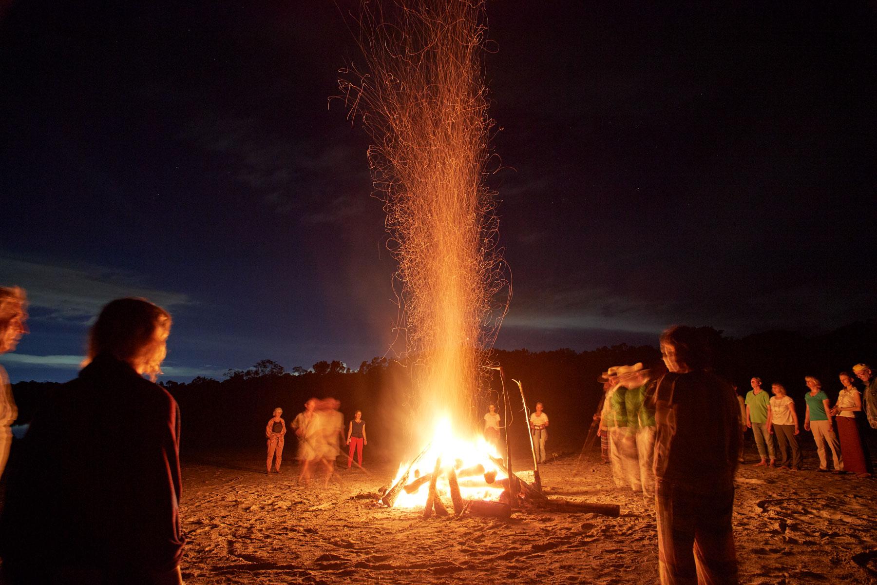 Bild eines großen loderndes Feuers mit dunkelblauem Wolkenhimmel und drumherum stehenden Menschen