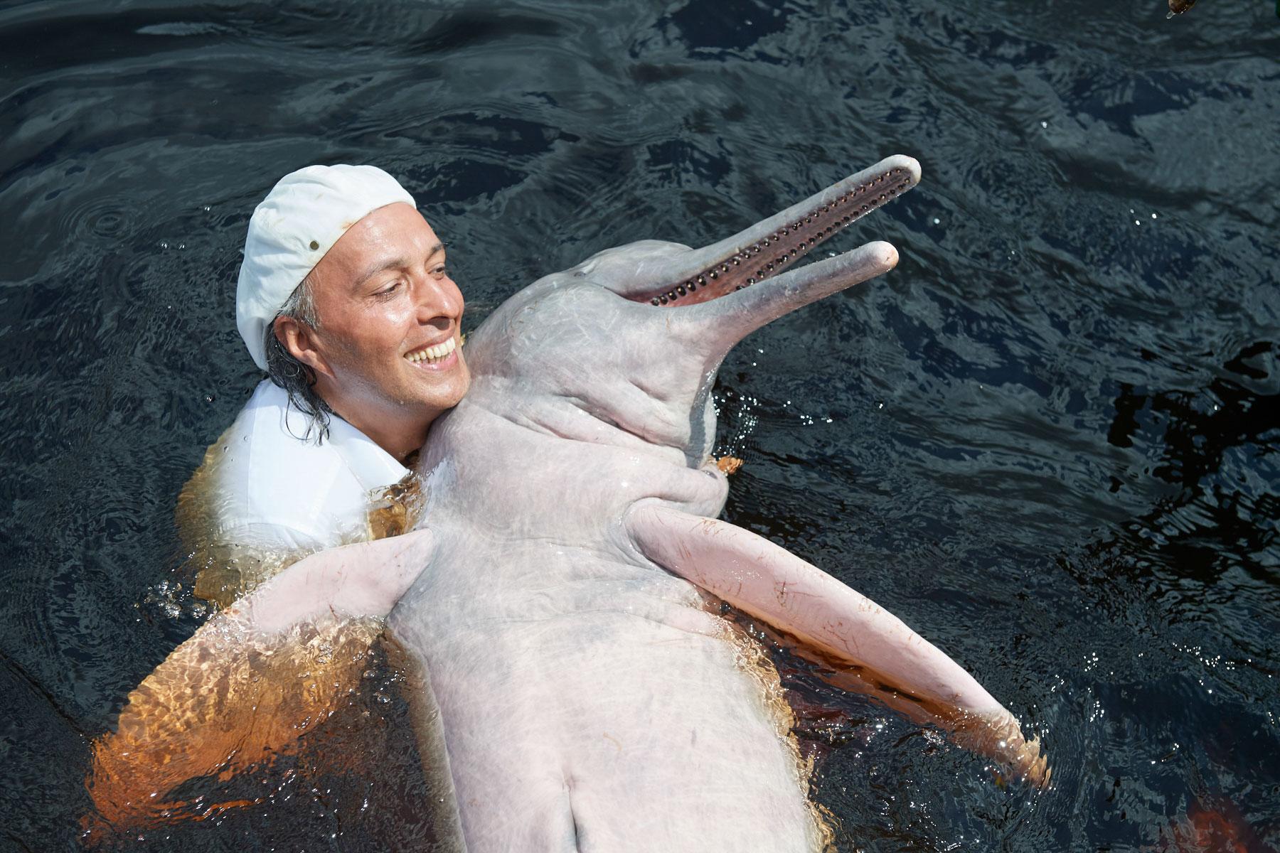 Mann spielt sehr innig mit einem roten Delphin im Rio Negro
