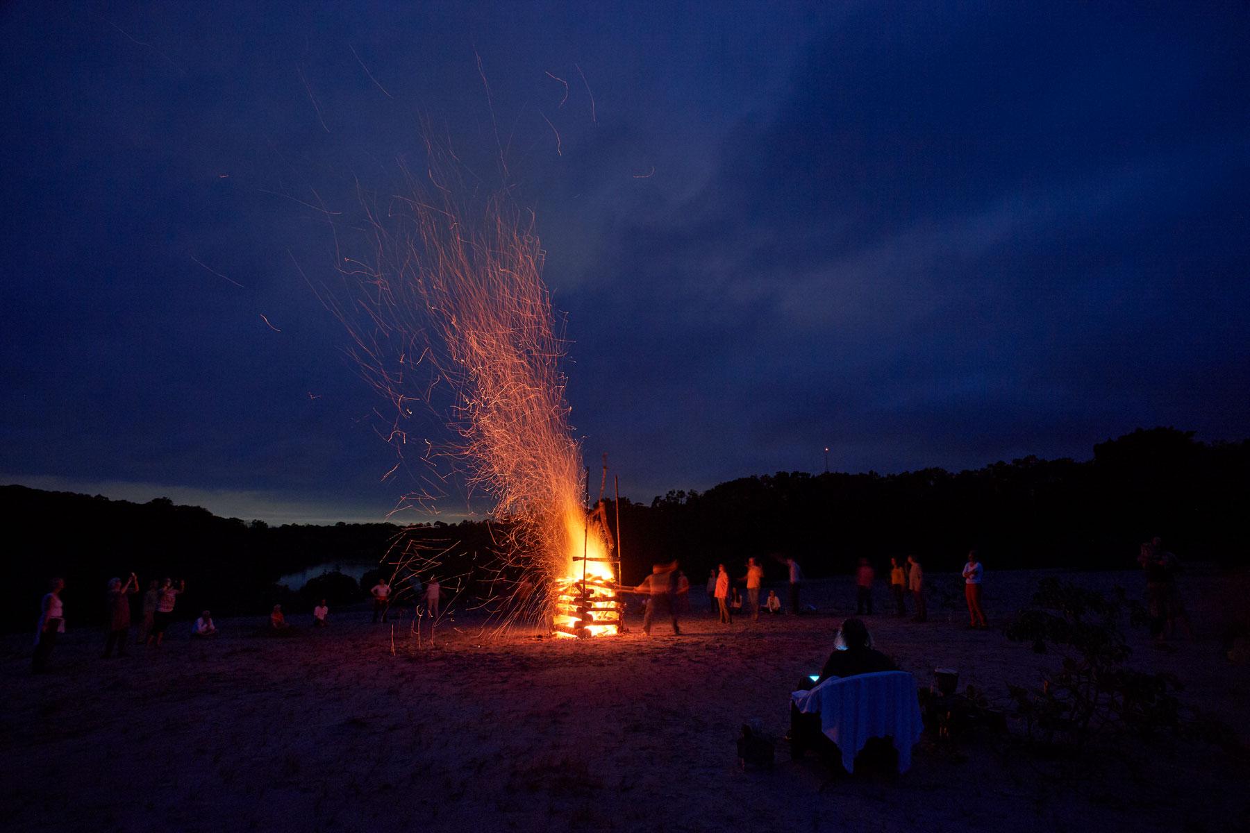 Bild eines großen Feuers mit dunkelblauem Wolkenhimmel und drumherum stehenden Menschen