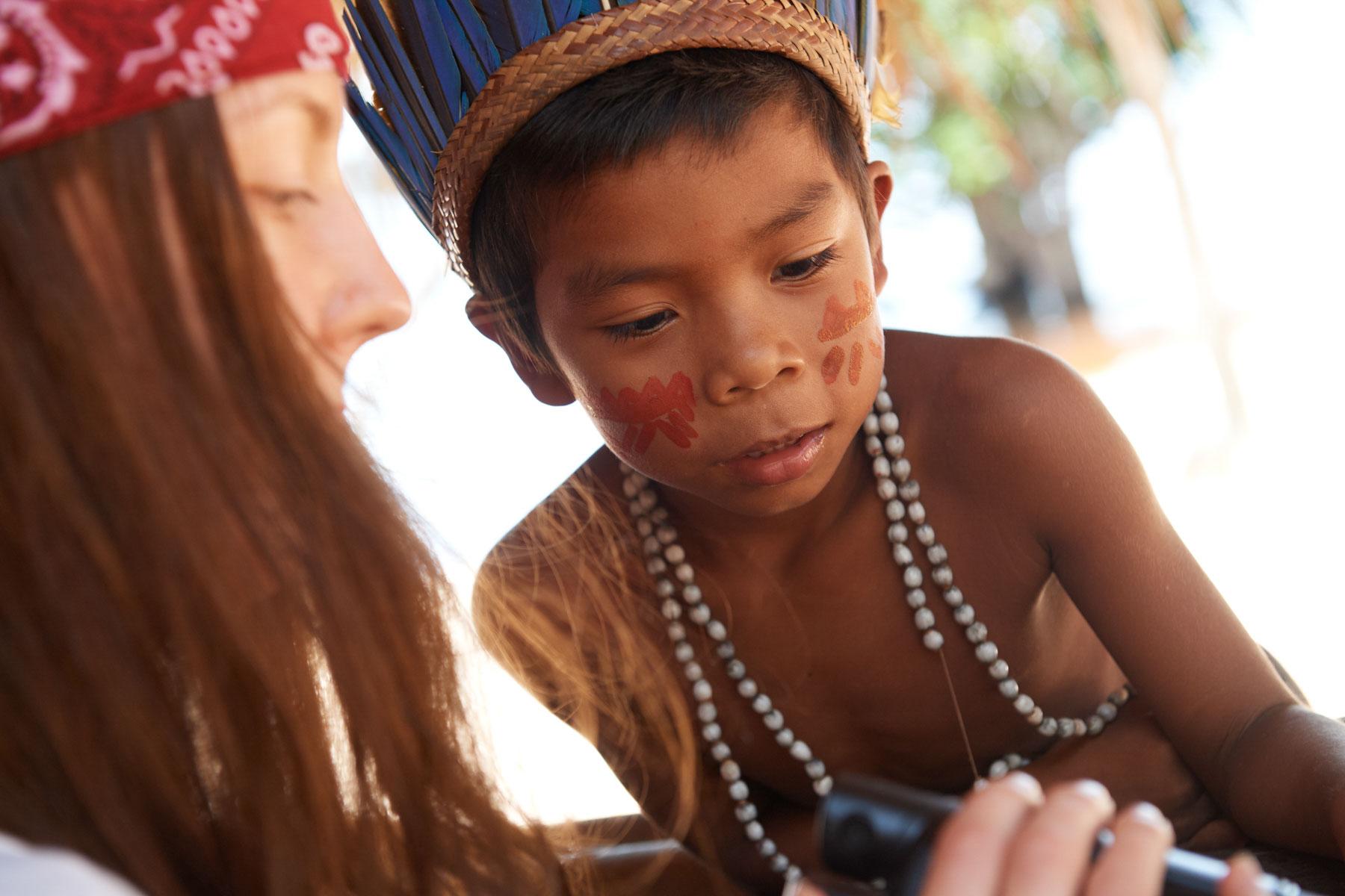 Bild eines indogenen Jungen mit Kopfschmuck und Bemalung der interessiert einer Weißen mit ihrer Kamera zuschaut