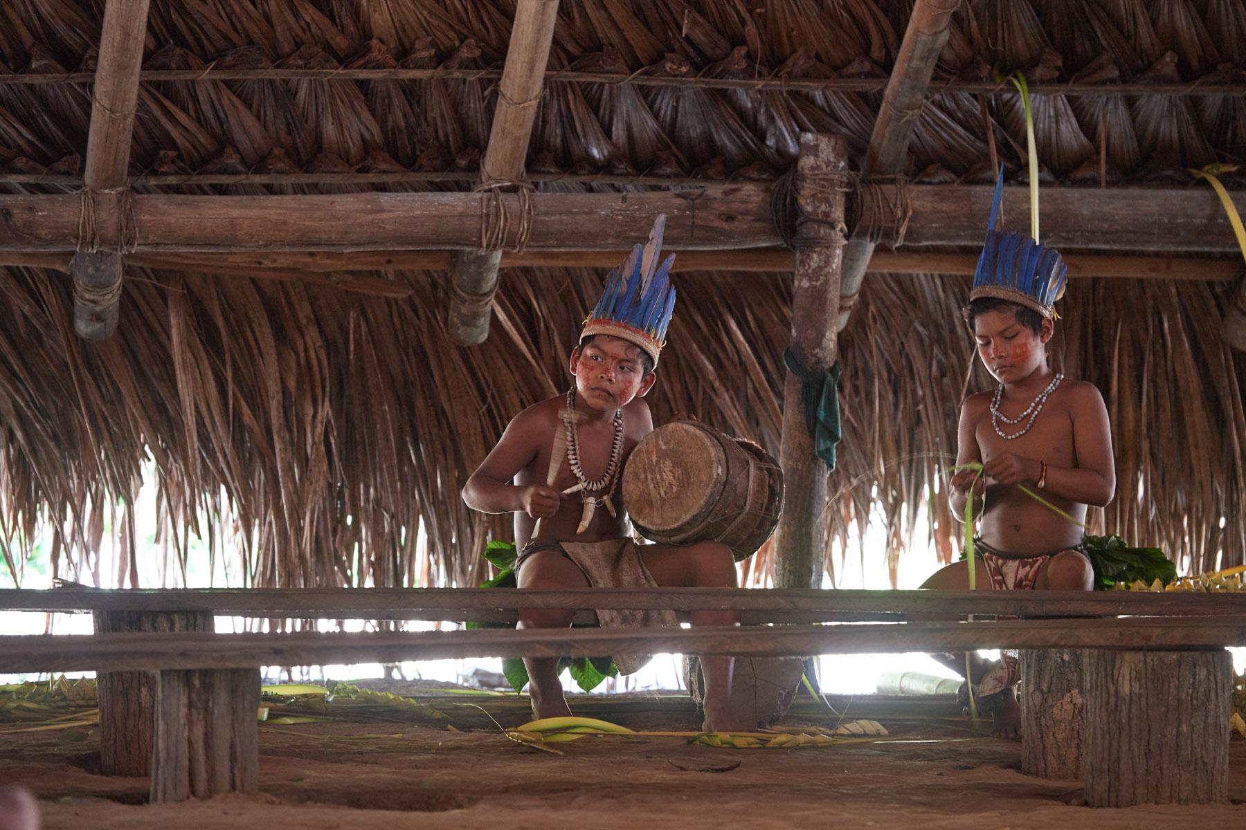 Bild zweier indogener Jungen mit Kopfschmuck und Bemalung beim trommeln und basteln