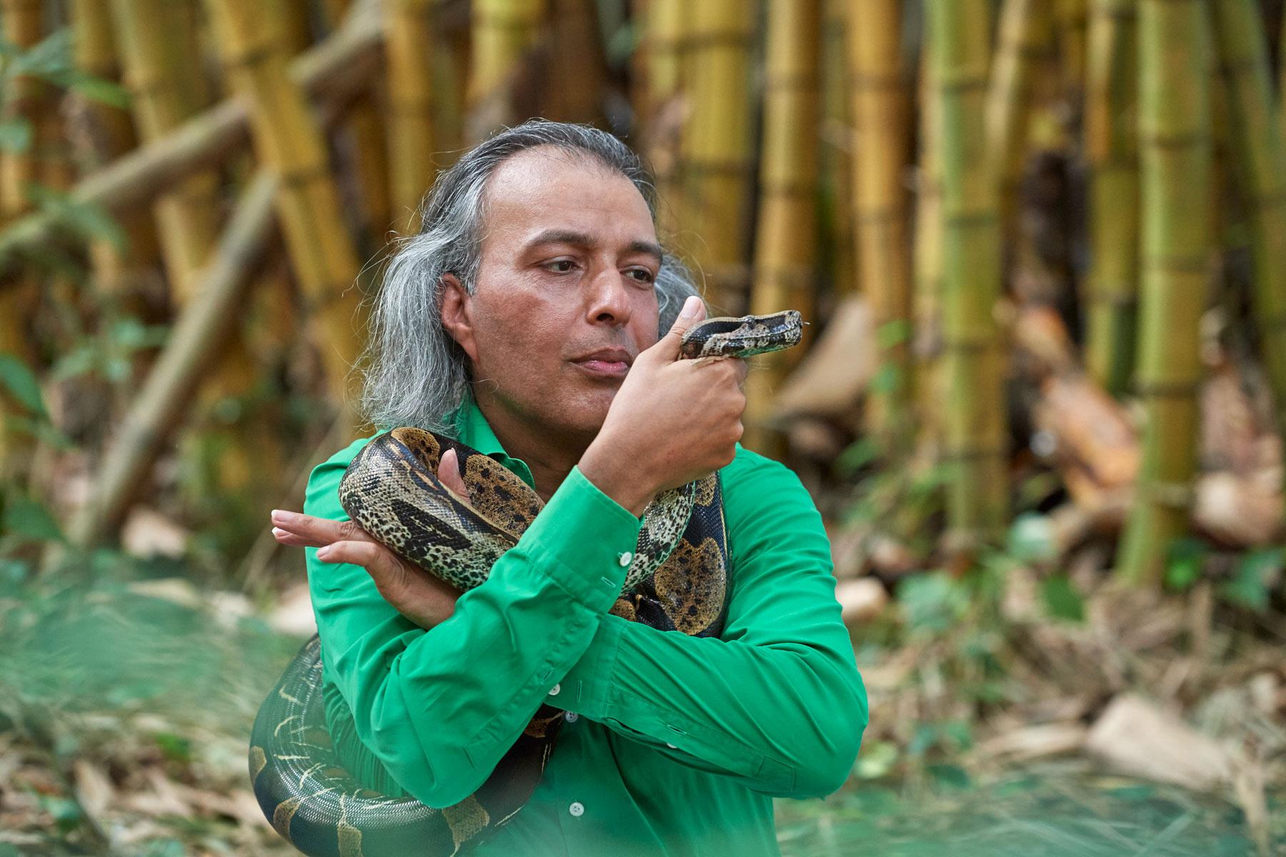 Mann in grünem Hemd kommuniziert mit einer um sich geschlungenen Riesenschlange