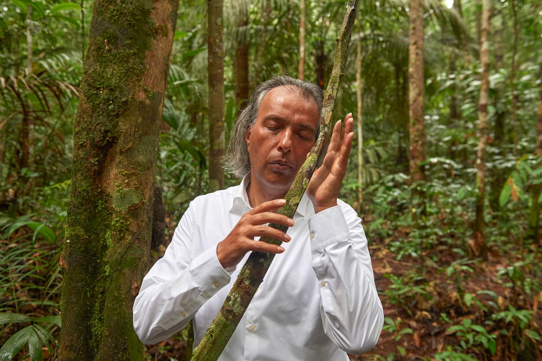 Heiliger Mann in weißer Kleidung fühlt und segnet ein Baumgewächs im Regenwald