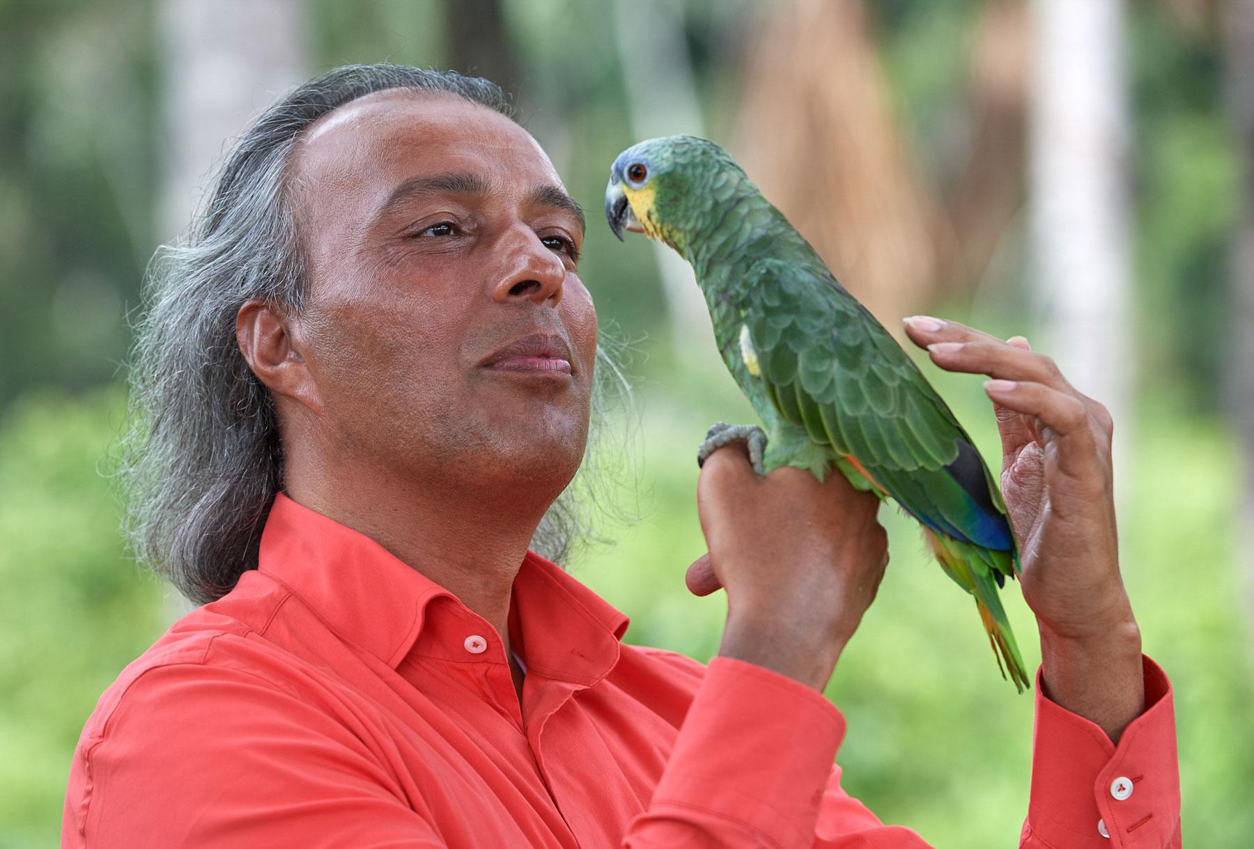 Mann in rotem Hemd kommuniziert liebevoll mit einem grünen Papagei