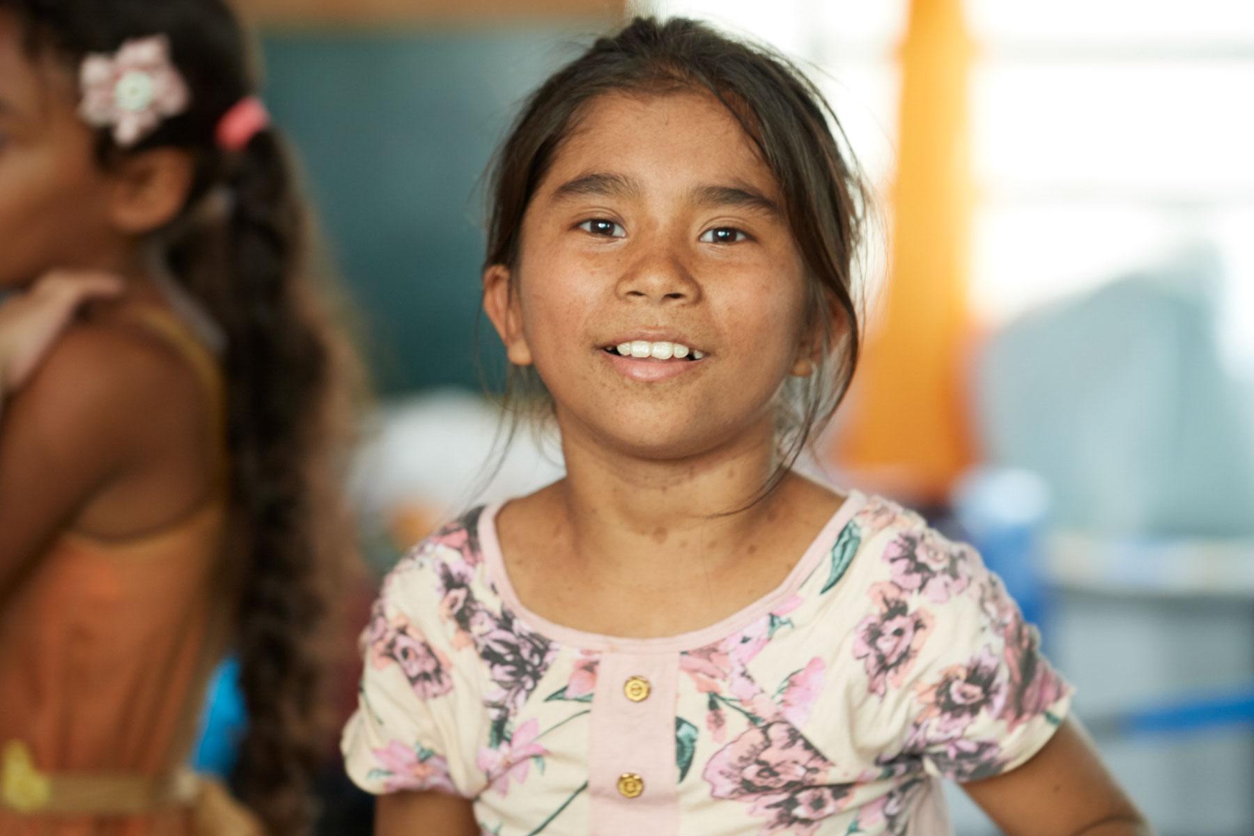 Bild einer jungen brasilianischen Schülerin, die freundlich in die Kamera schaut