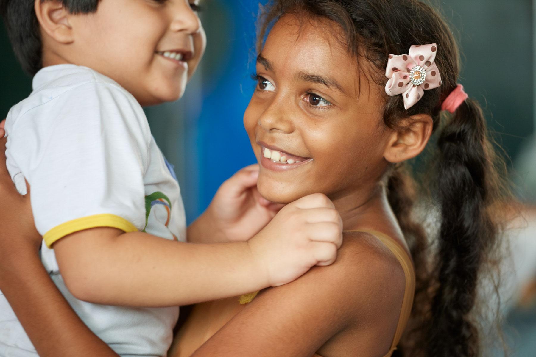Bild einer brasilianischen Schülerin die mit einem kleinen Jungen trollt