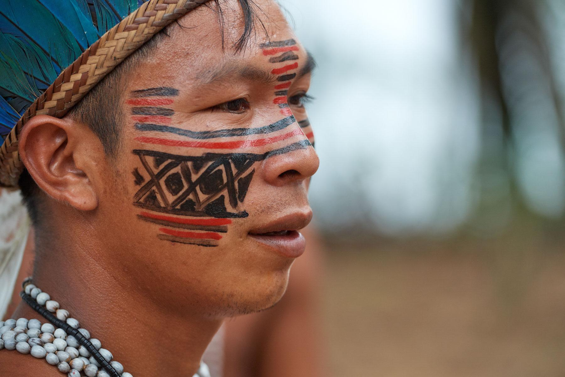 Portrait eines jungen Indigos mit Kopfschmuck und Bemalung beim Gespräch