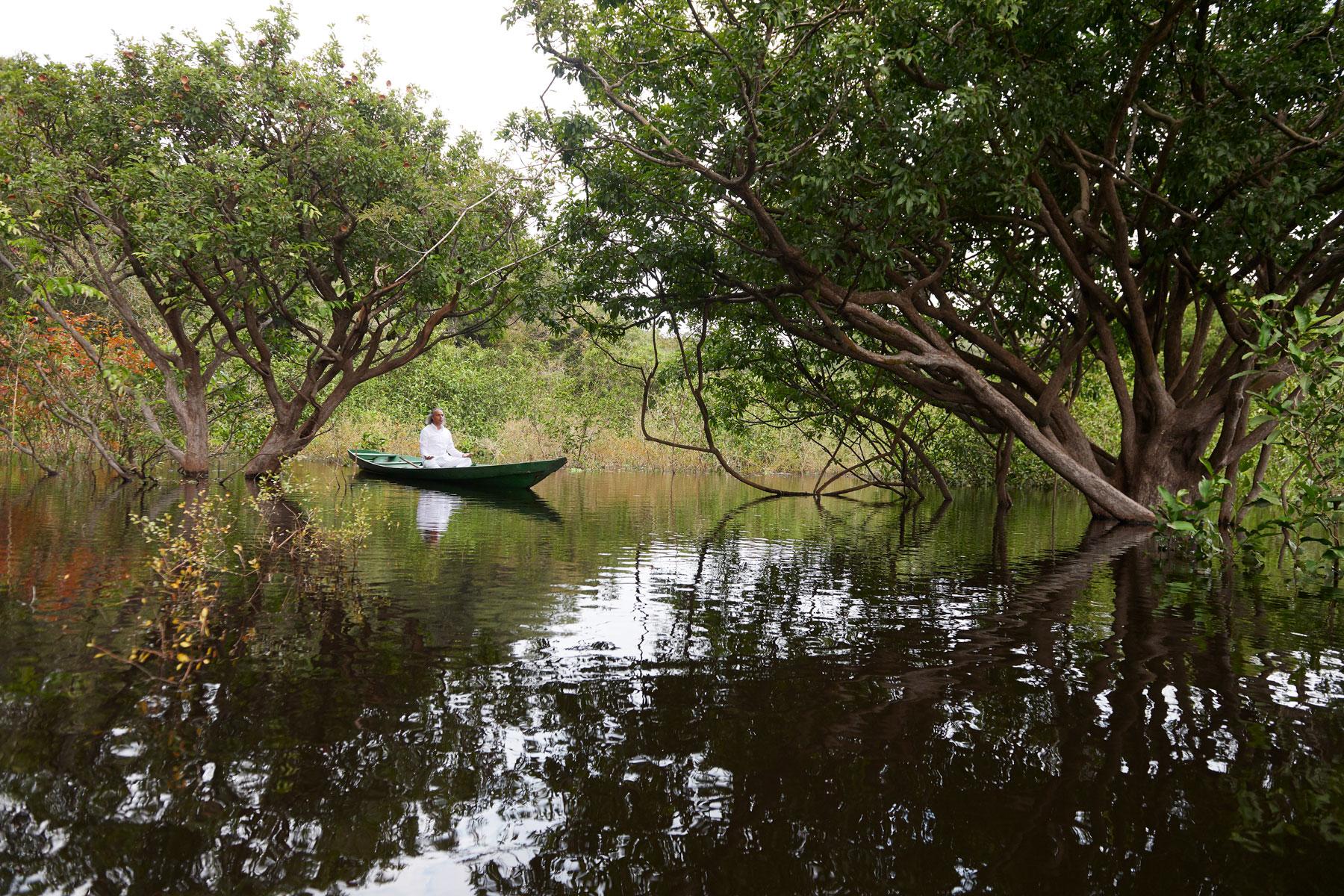 Foto einer stillen Nebenflusslandschaft des Rio Negro mit einem im Boot sitzenden meditierenden Mannes in Weiß