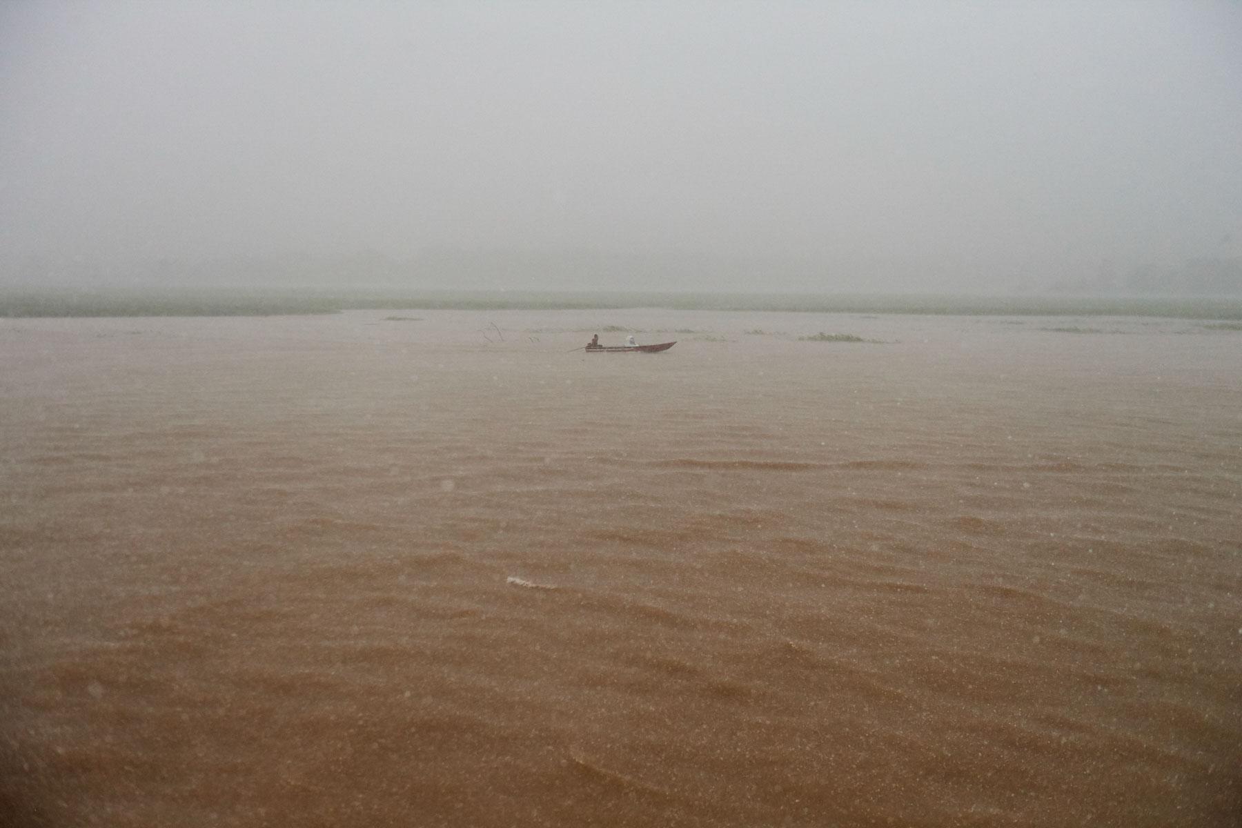 Foto zeigt die braune Flusslandschaft mit Boot des Rio Negro bei schwerem Regenschauer