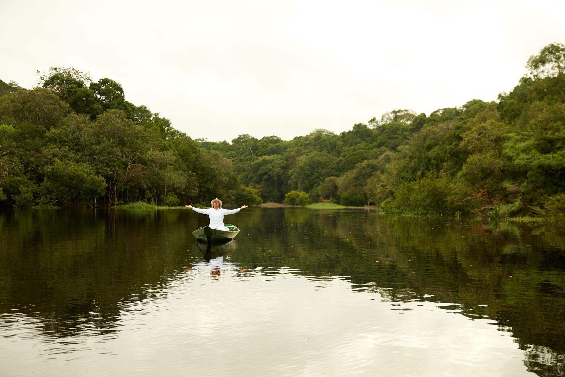 Foto eines Mannes in Weiß mit ausgebreiteten Armen in einem Holzboot sitzend, das Wasser und den umliegenden Regenwald segnet