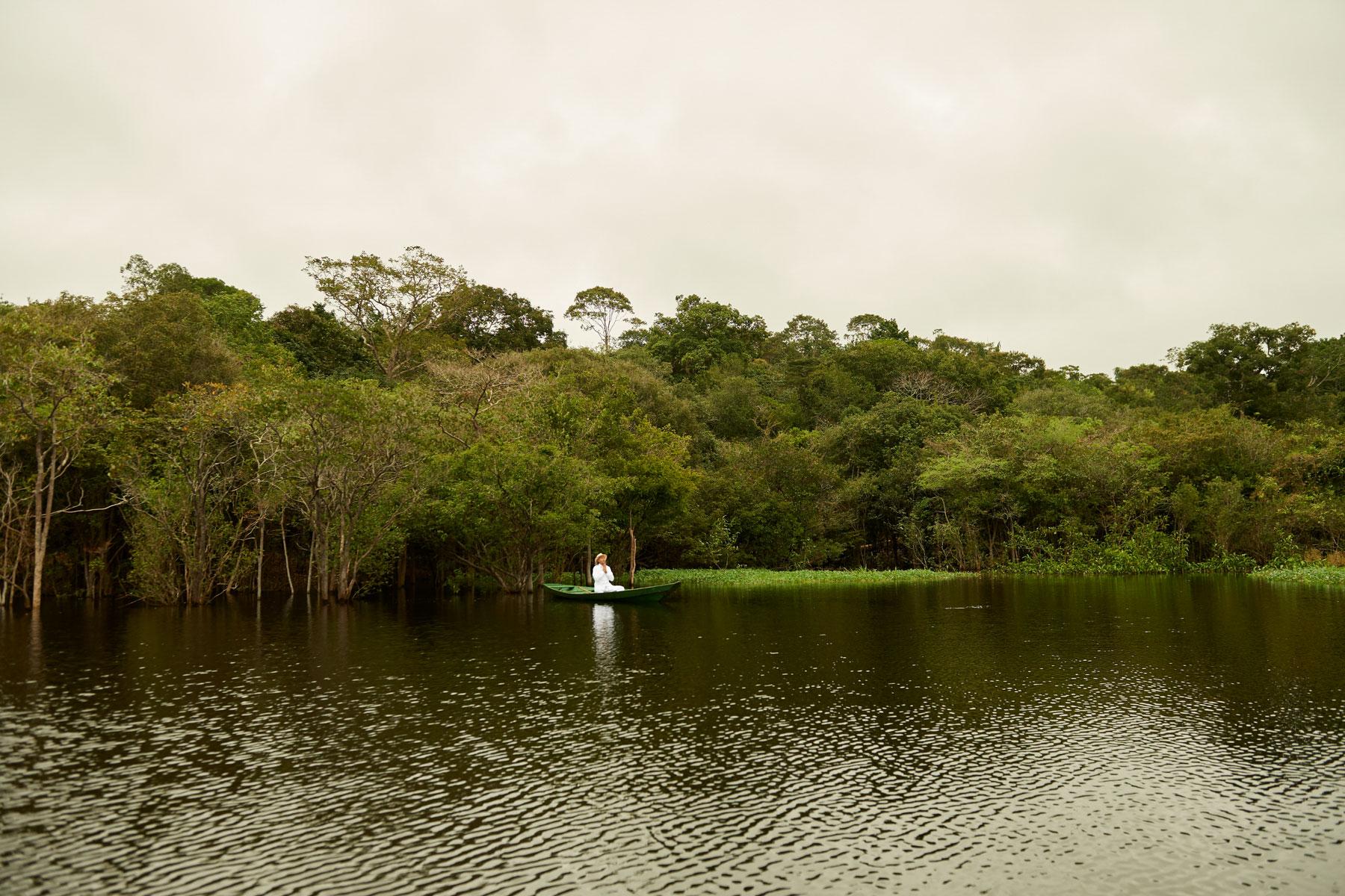 Foto eines Mannes in Weiß in einem Holzboot sitzend, das Wasser und den umliegenden Regenwald segnet und innehält