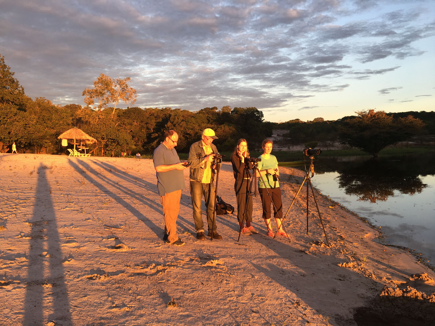 Foto einer Vierergruppe, bei sehr schräg stehender Sonne am Ufer der Rio Negro