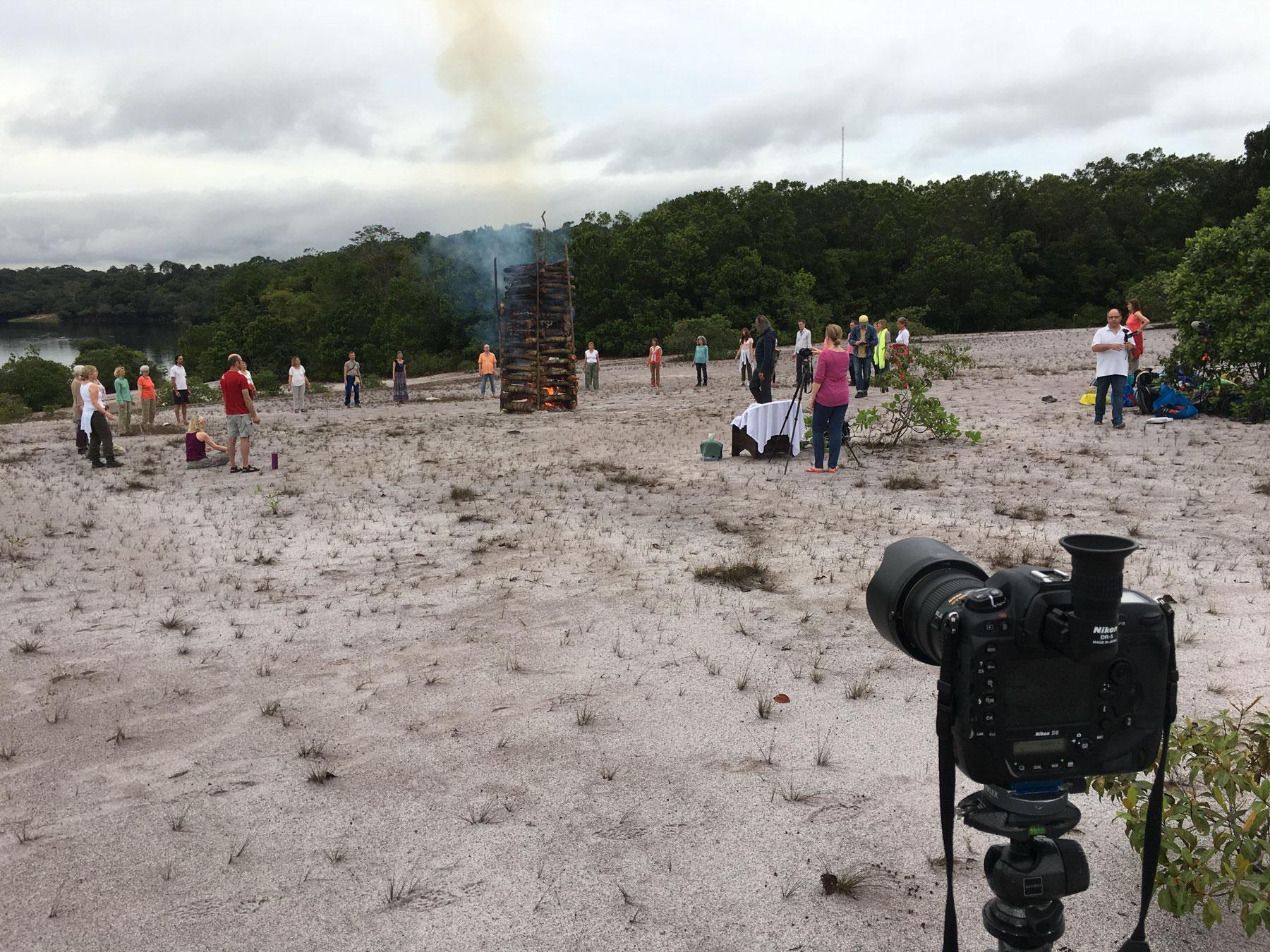 Foto einer Gruppe, die im Kreis um ein Feuer stehen mit einer Kamera im Vordergrund
