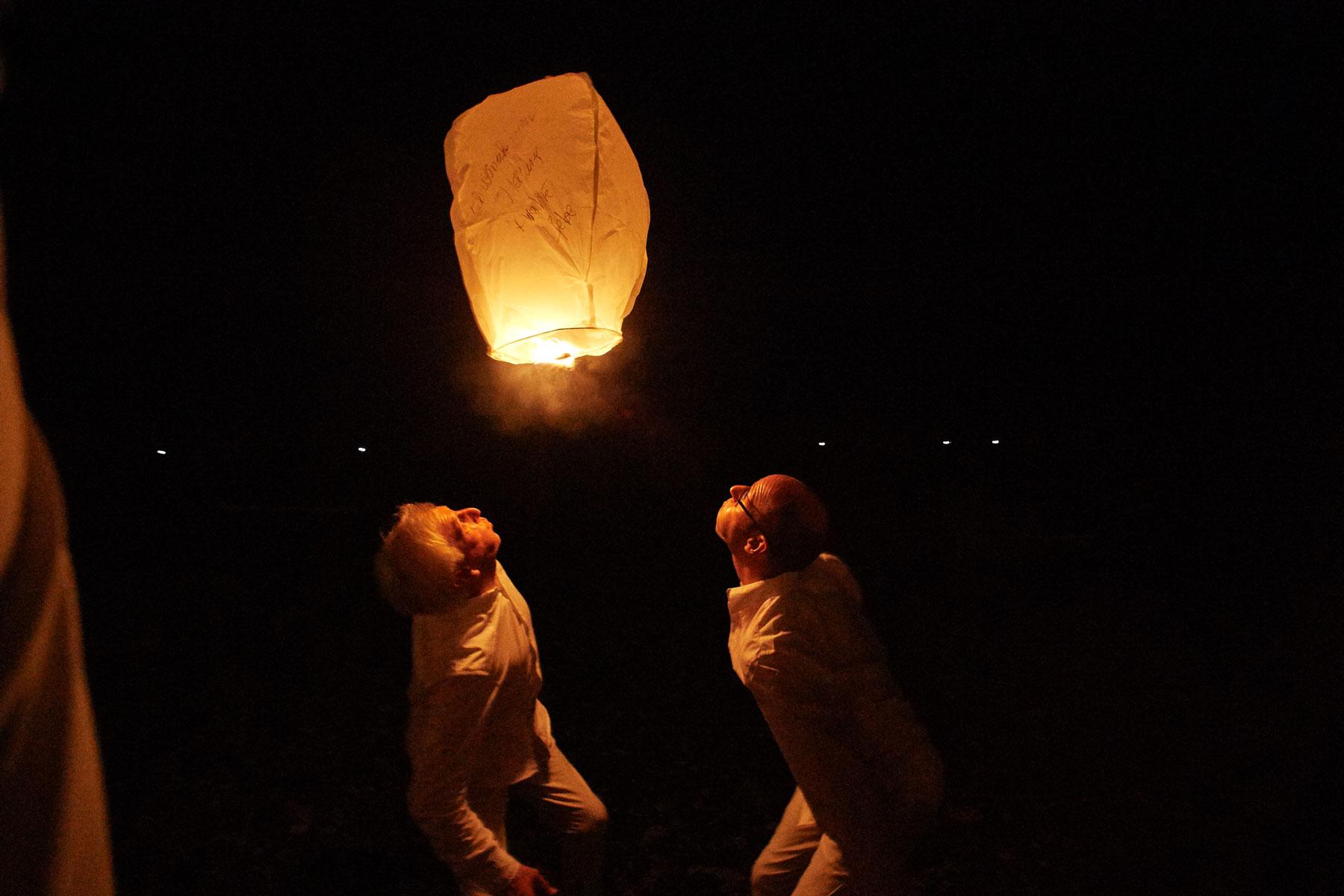 Nächtliches Foto zweier Männer, die einen Papierballon von unten anpusten