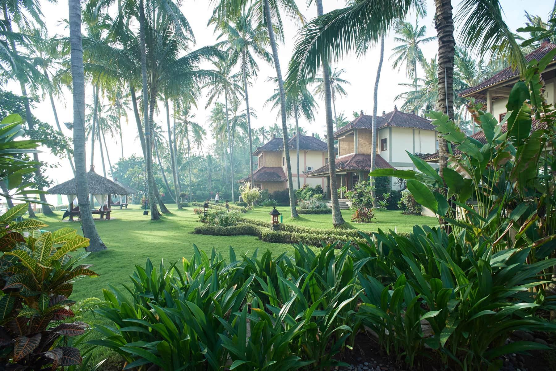 Das Foto zeigt eine sehr gepflegte Hotelanlage mit schöne Palmen und Gästehäusern in zarten Sonnenlicht