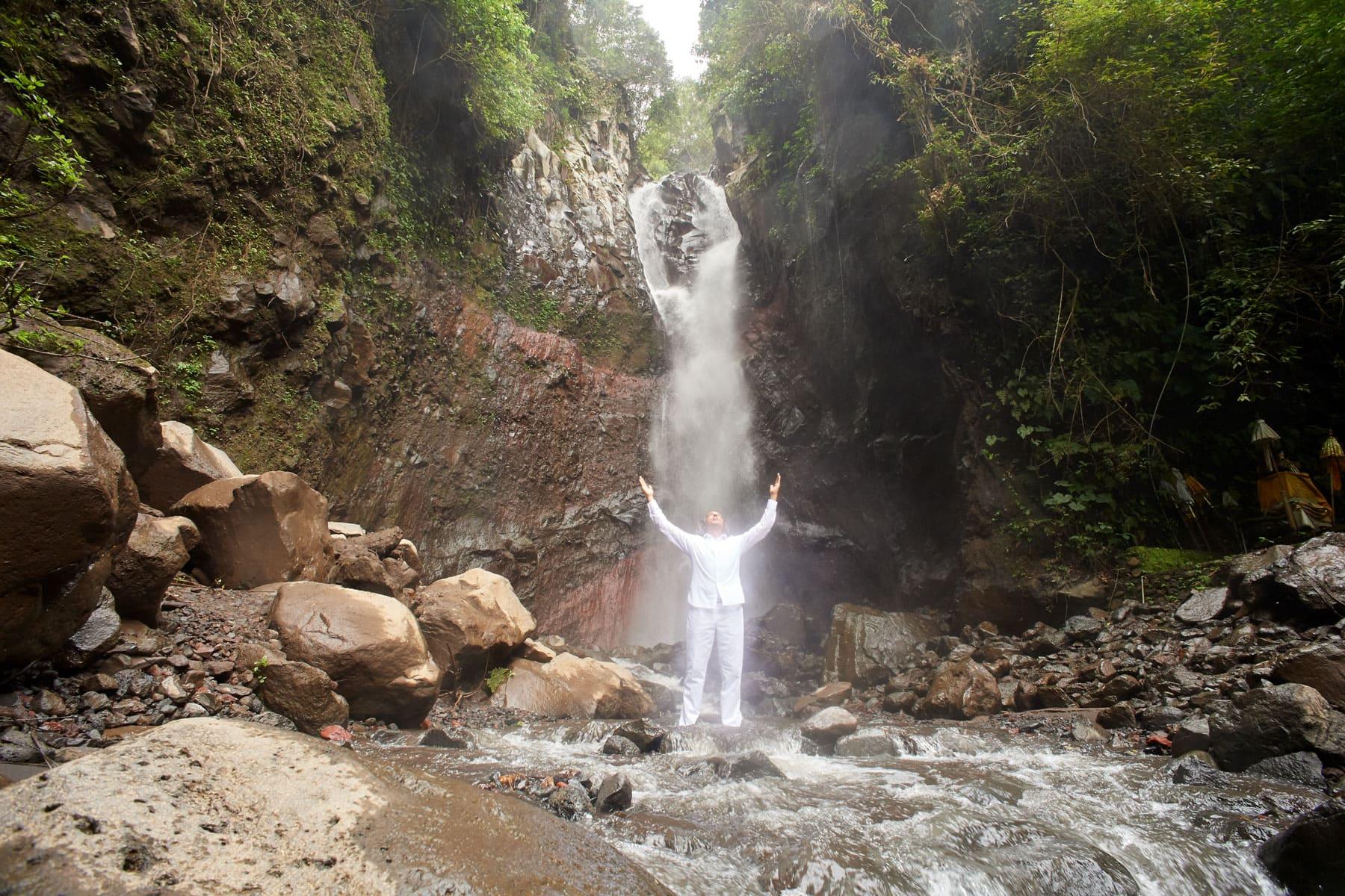 Fotografie eines Mannes in weißer Kleidung vor einem Wasserfall segnend
