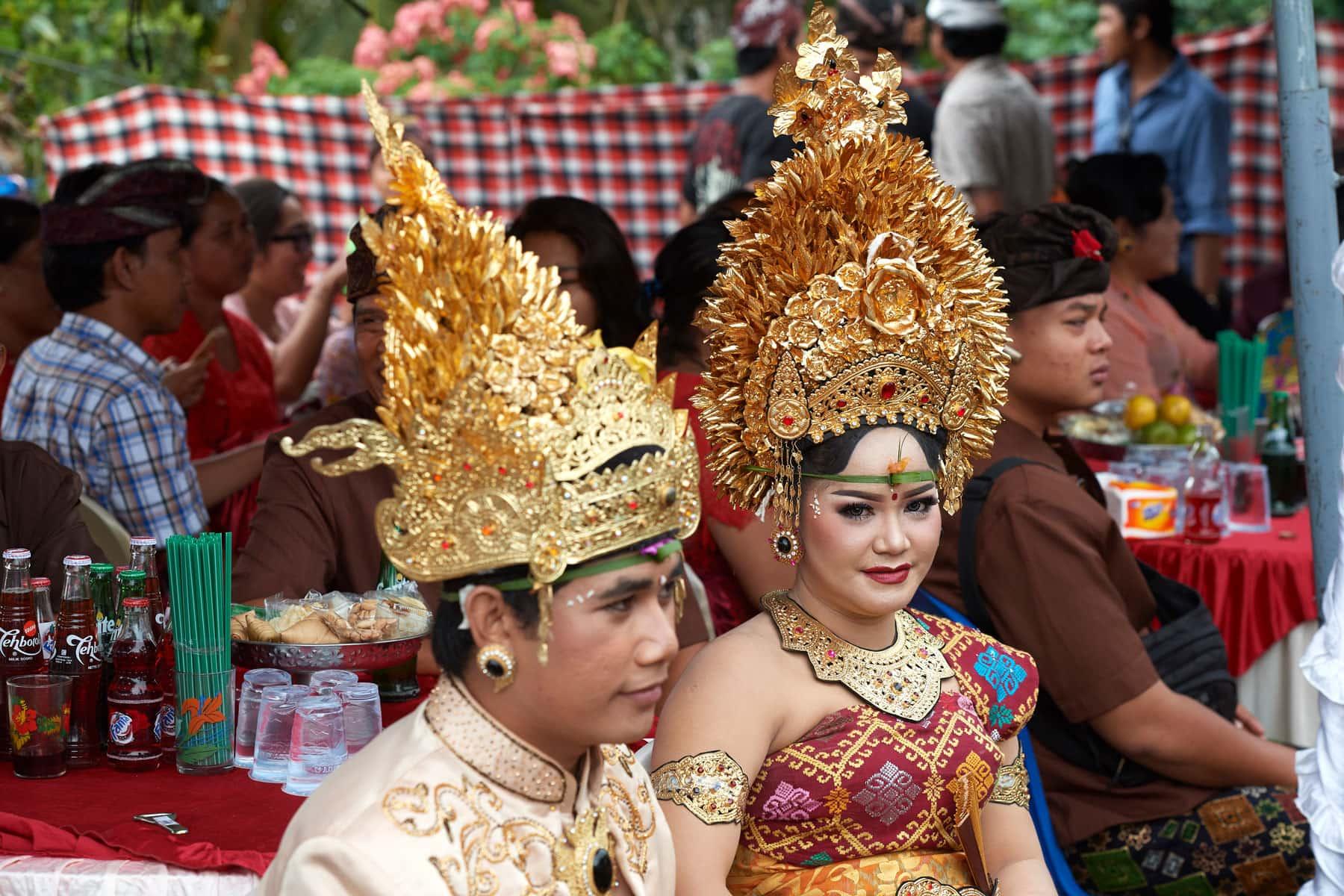 Das Foto zeigt eine balinesische Hochzeitsfeier bei das Hofer chzeitspaar im Vordergrund zu sehen ist