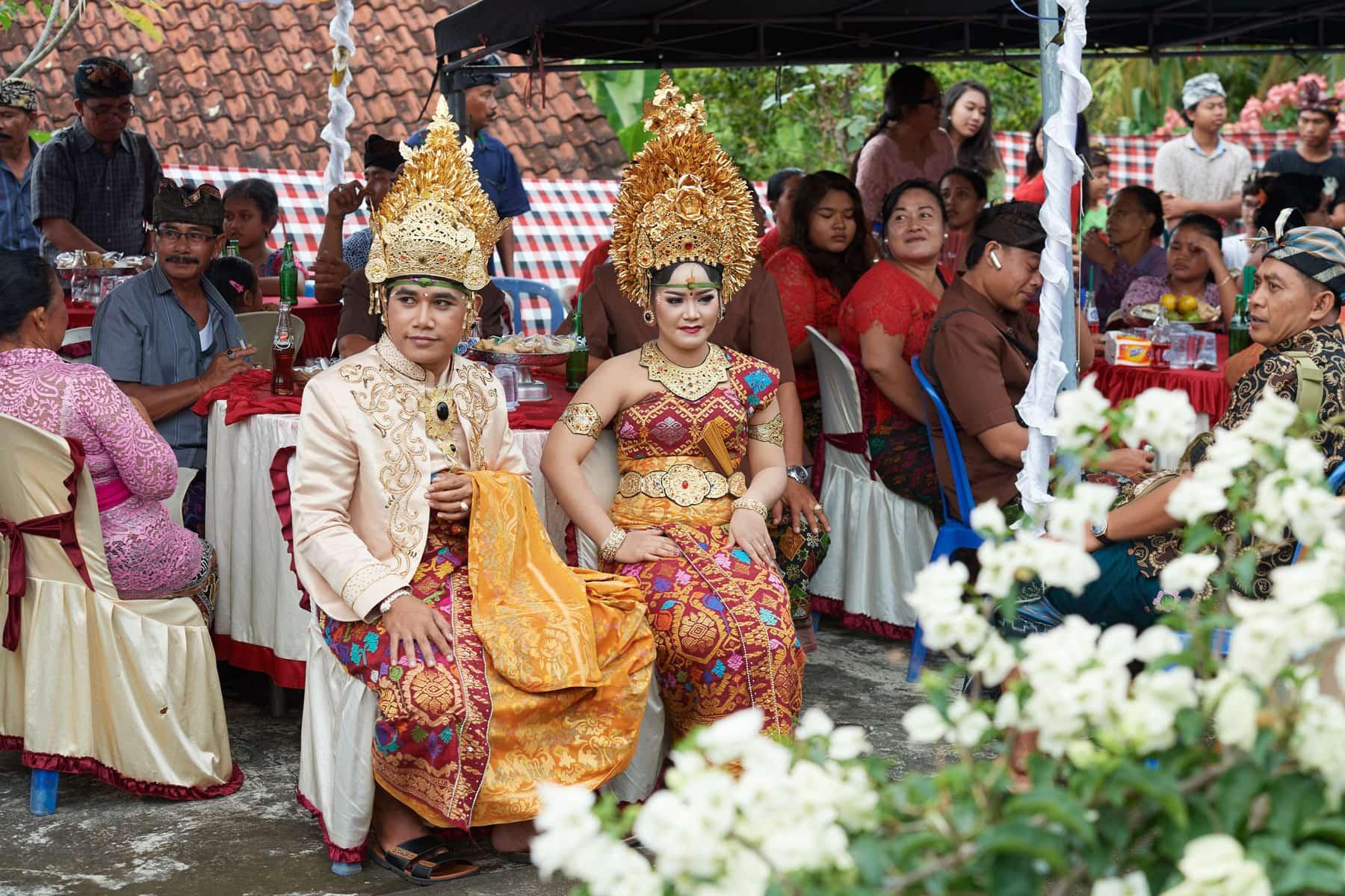 Das Foto zeigt eine balinesische Hochzeitsgesellschaft, bei dem das Hochzeitspaar im Vordergrund zu sehen ist