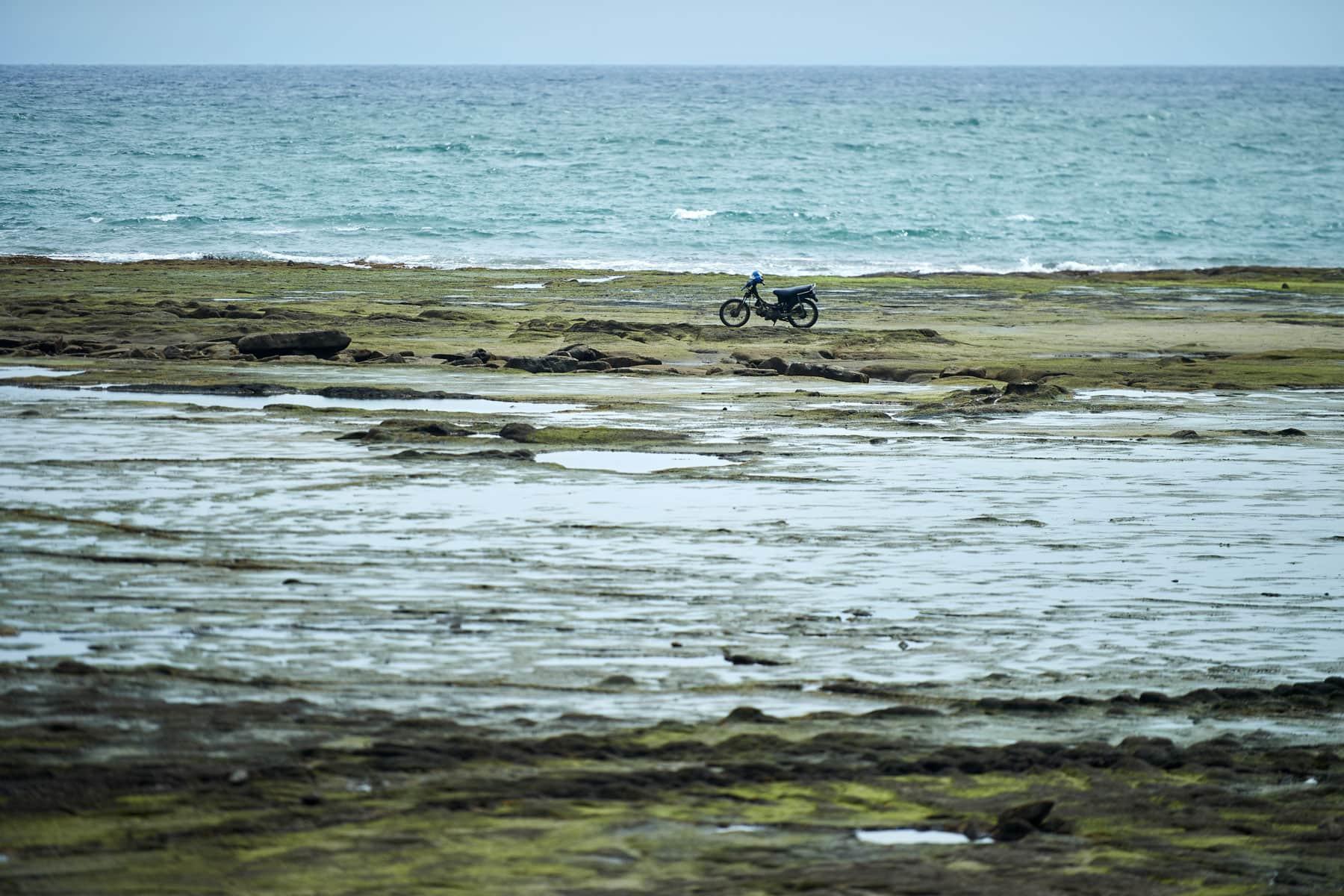 Bild einen einsam am Meer stehenden Mopeds