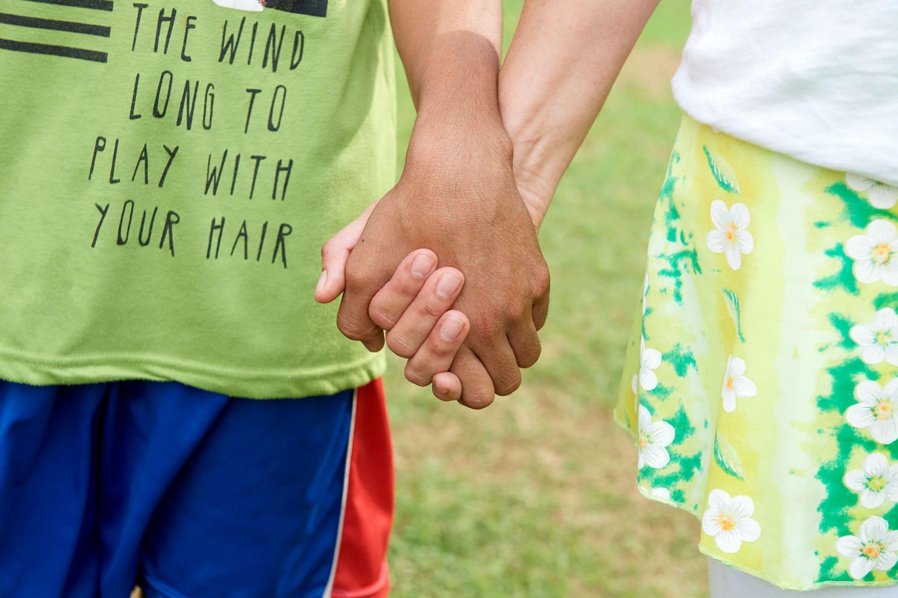Das Foto zeigt, wie sich ein weißes und ein braunes Kind wie sie sich die Hände geben