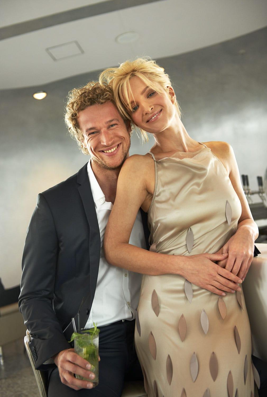 Portrait eines gut aussehenden Paares in einer Bar die gelassen und freudestrahlend in die Kamera blicken