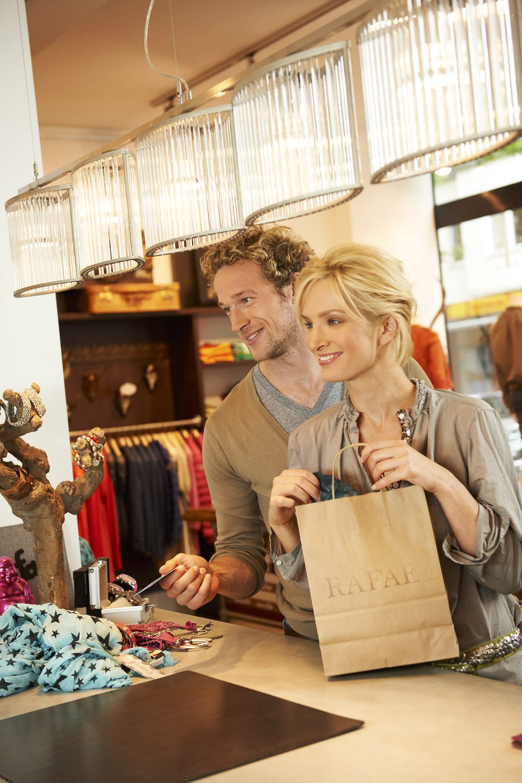 Portrait eines gut situierten Paares, dass in einer anspruchsvollen Boutique bezahlen möchte