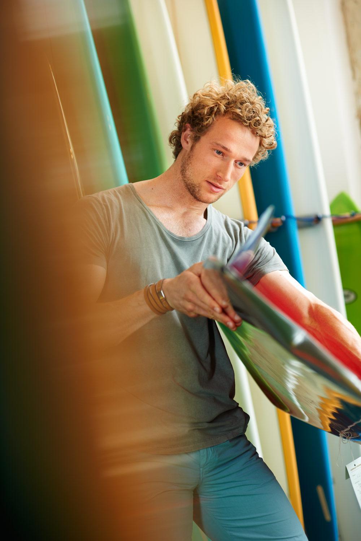 Portrait eines jungen Mannes der ein Surfbrett inspiziert