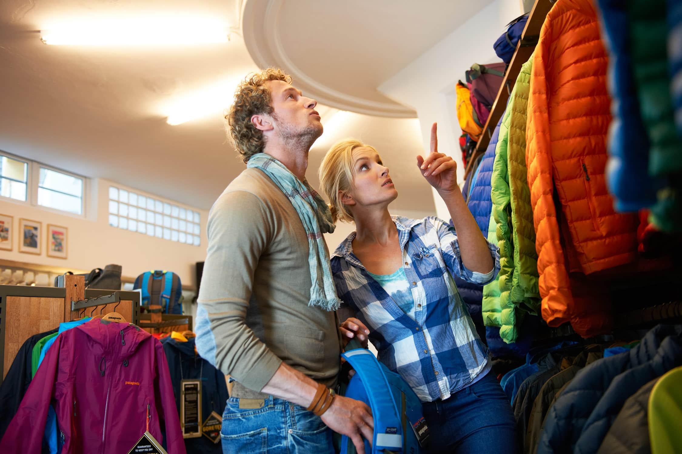 Portrait eines sportlichen Paares, dass interessiert in einem Outdoorladen nach passenden Kleidungsstücken sucht